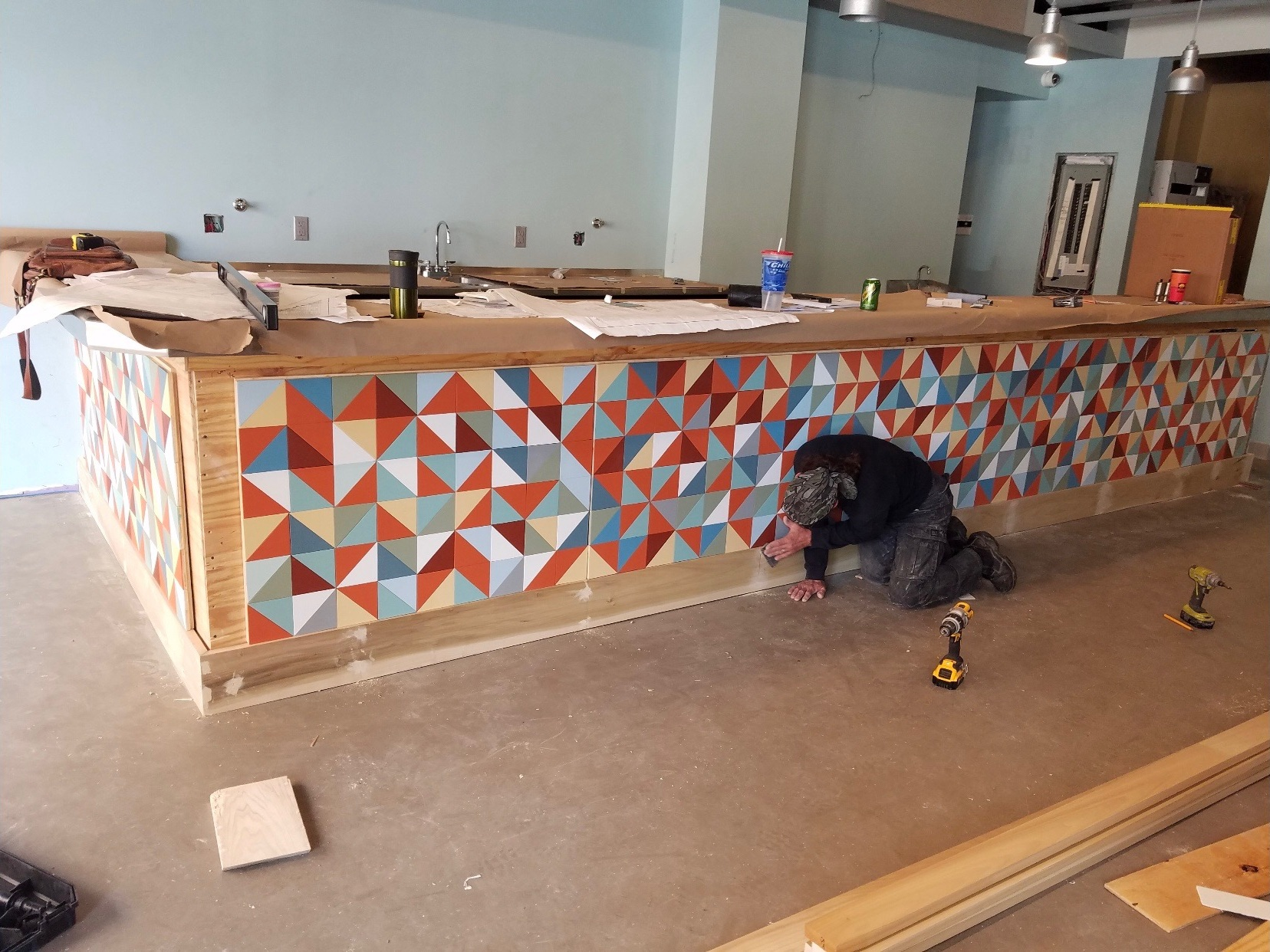 Carpenter trimming out the bar after installation.