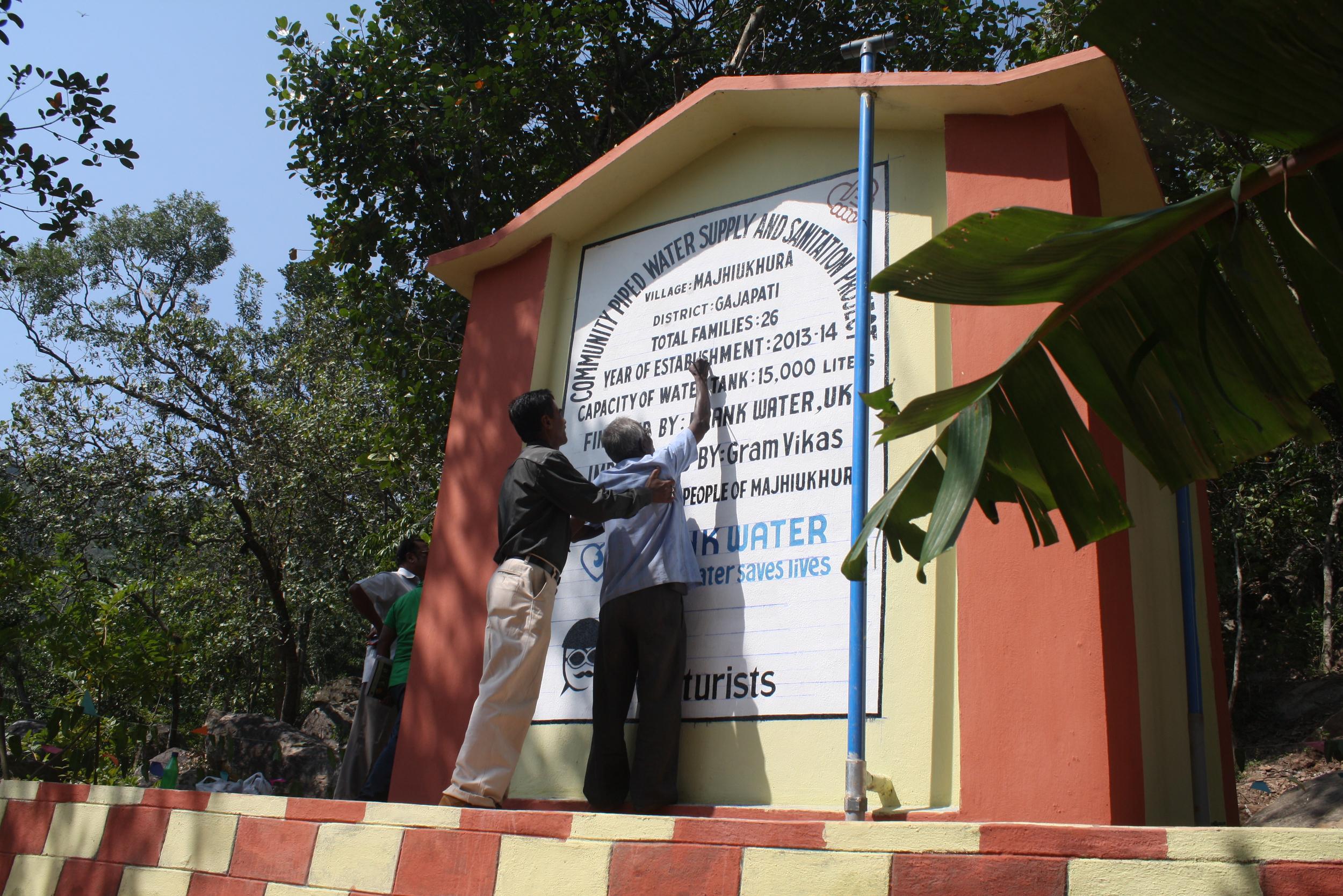 Kailash Sahu, field coordinator with Gram Vikas helping the old painter finish the last bit of work on the water tank. Photography: Praveena Sridhar, FRANK Water India Coordinator