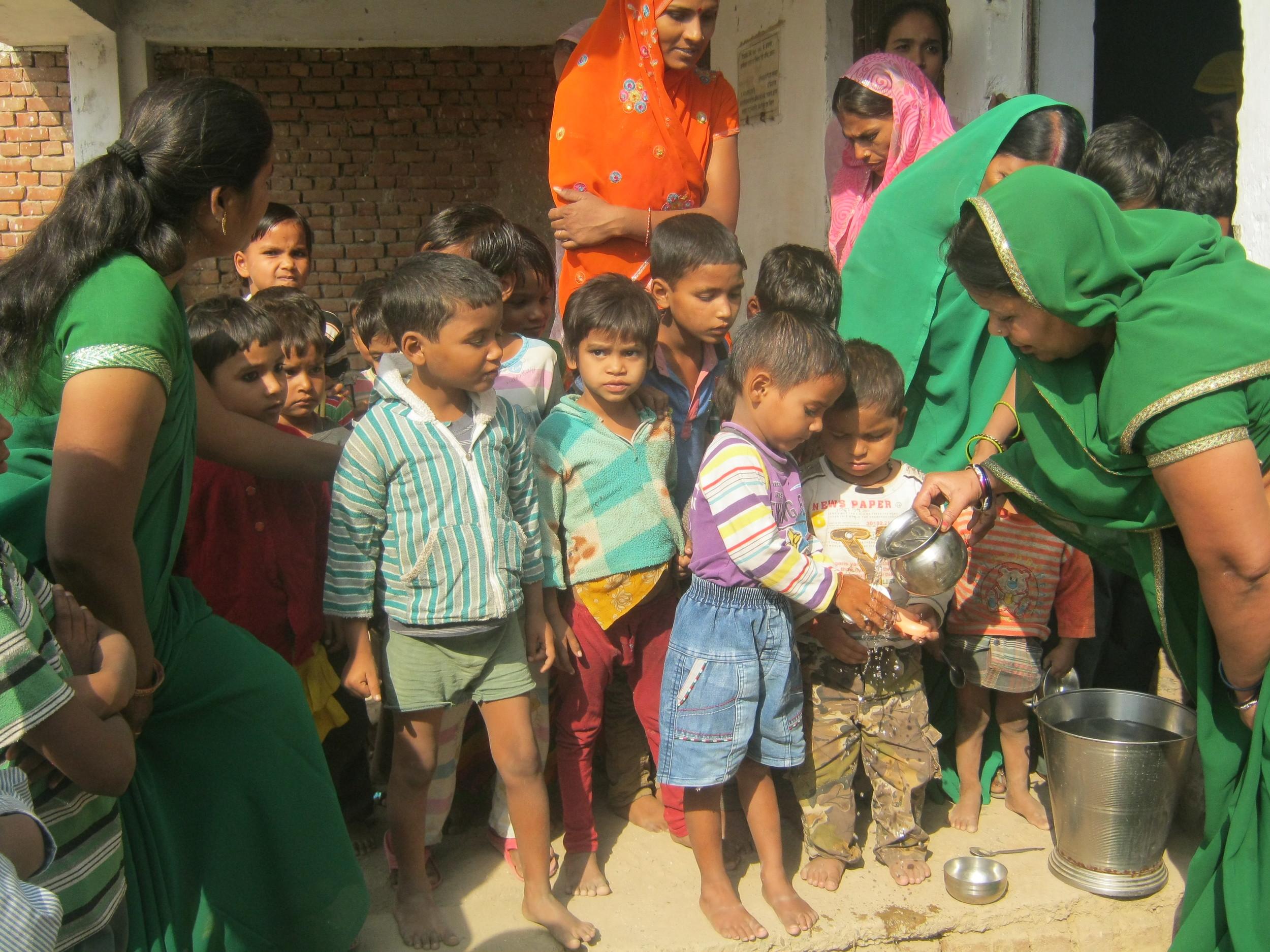 demonstrating handwashing to children