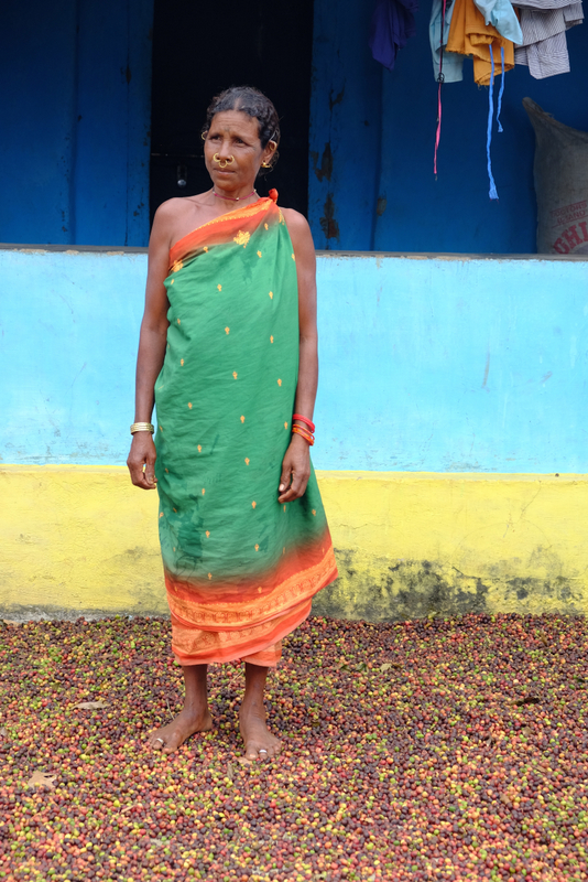 Korrabatti with coffee coffee drying under her feet in front of her house