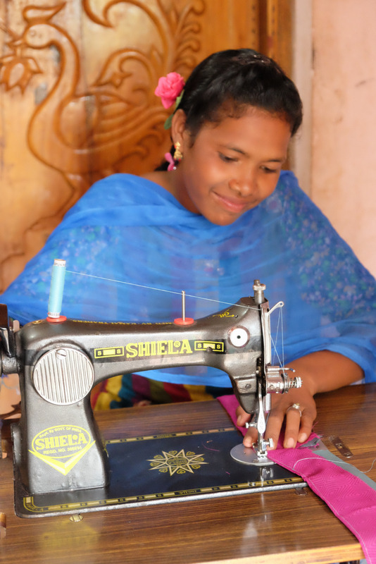 Neela at work in her own tailoring business
