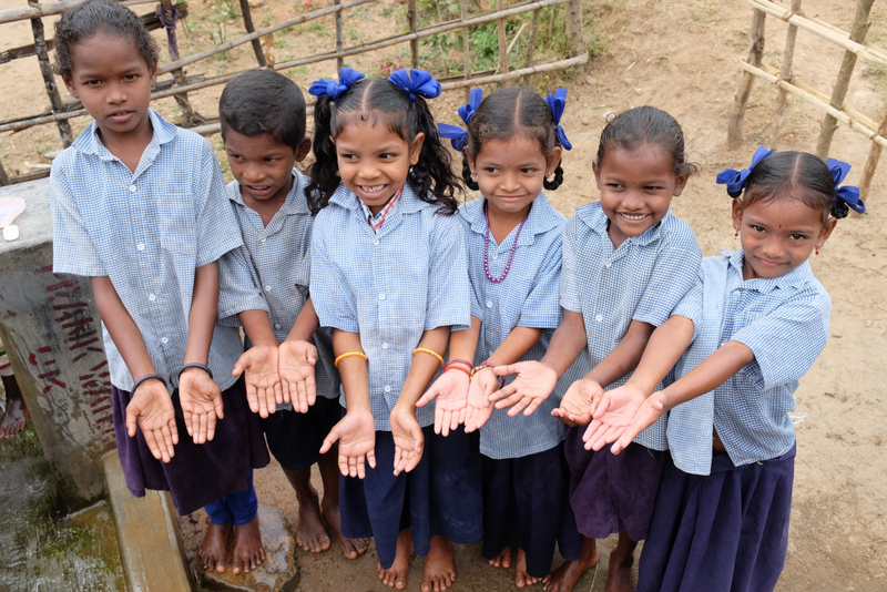 Children show off their clean hands after their handwashing session