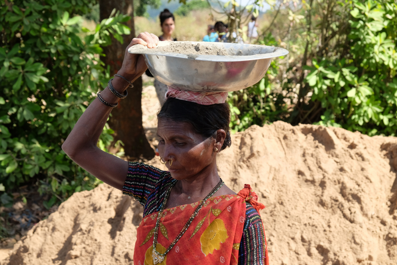 Woman carrying bowl of cement