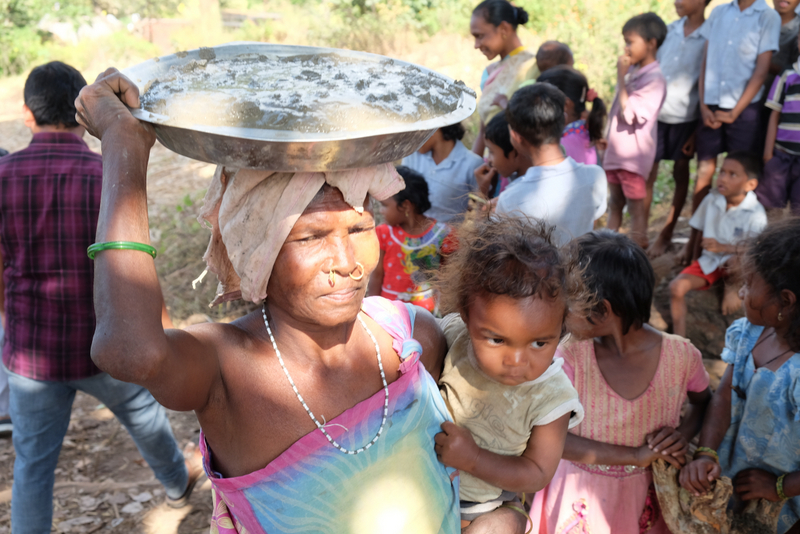 A woman carries a bowl of cement and her baby