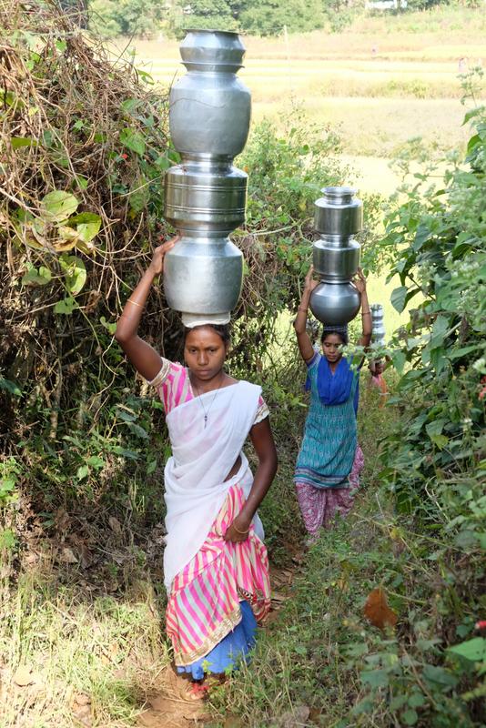 Women carrying water up a narrow, winding path.