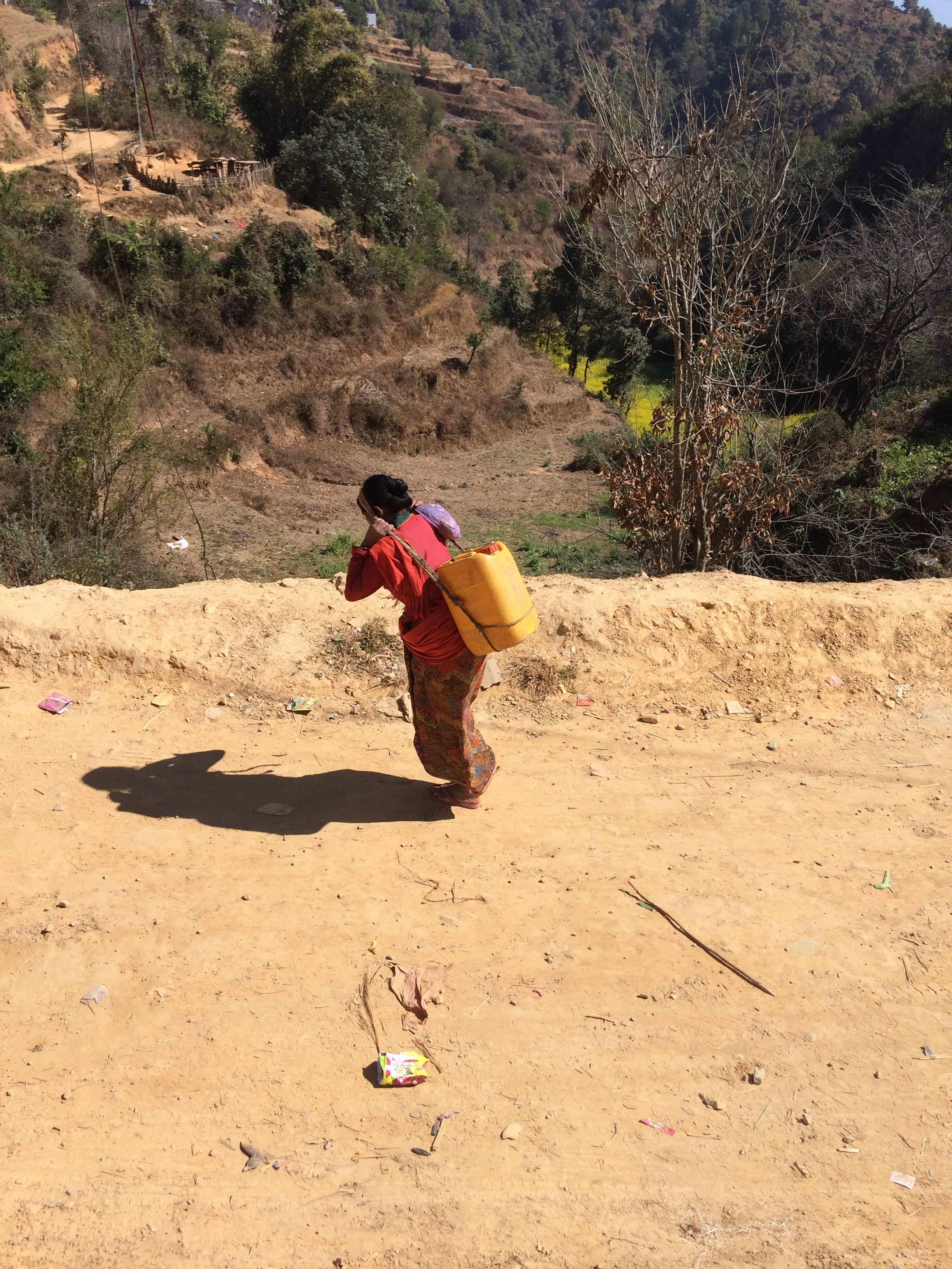 A woman carries dirty water from the bottom of the hill back to her home at the top