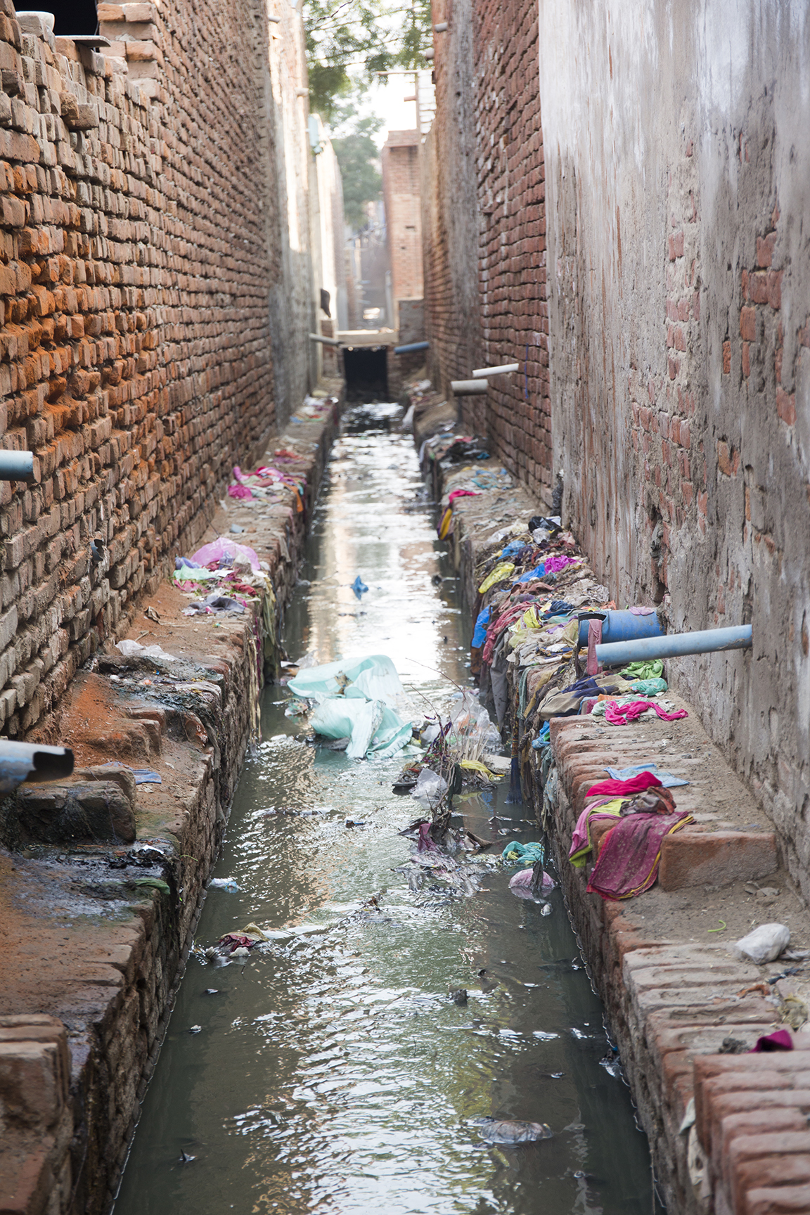 Open Sewer runs behind houses in Agra, India