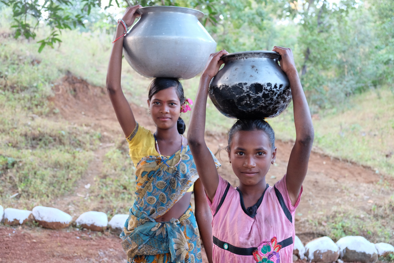 Girls carry water on their heads