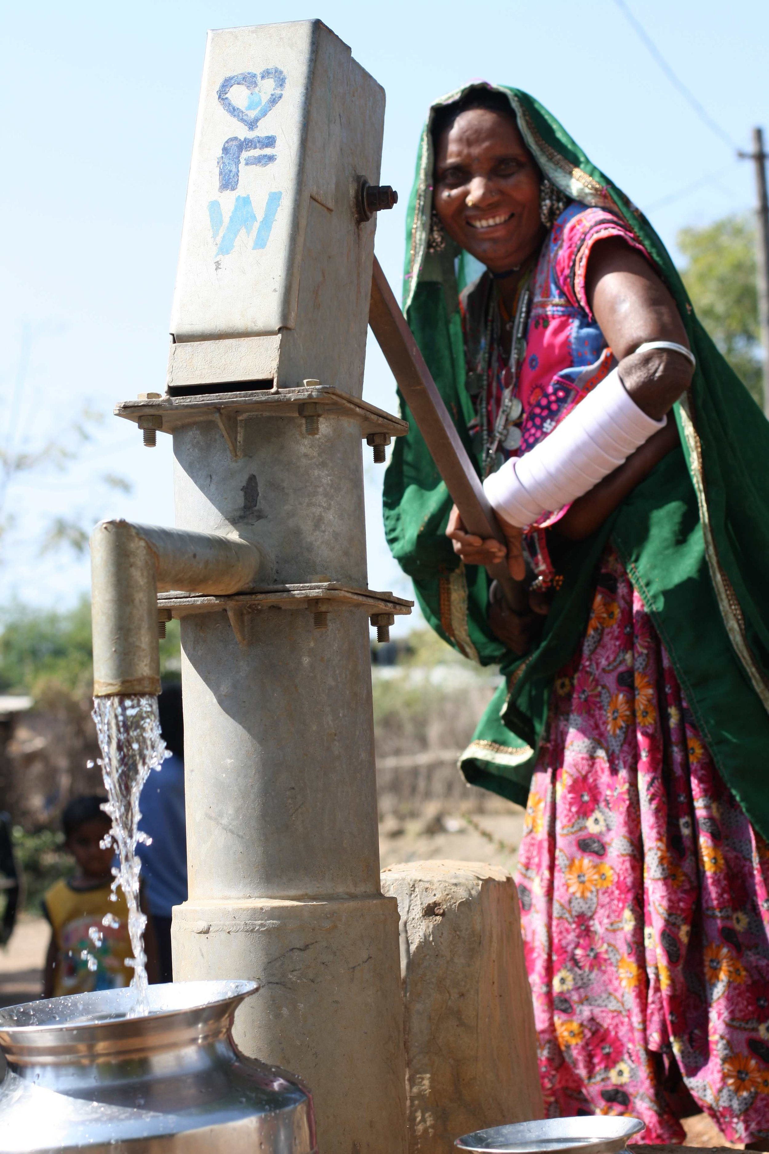 Tribal woman collects water from a FRANK Water hand pump