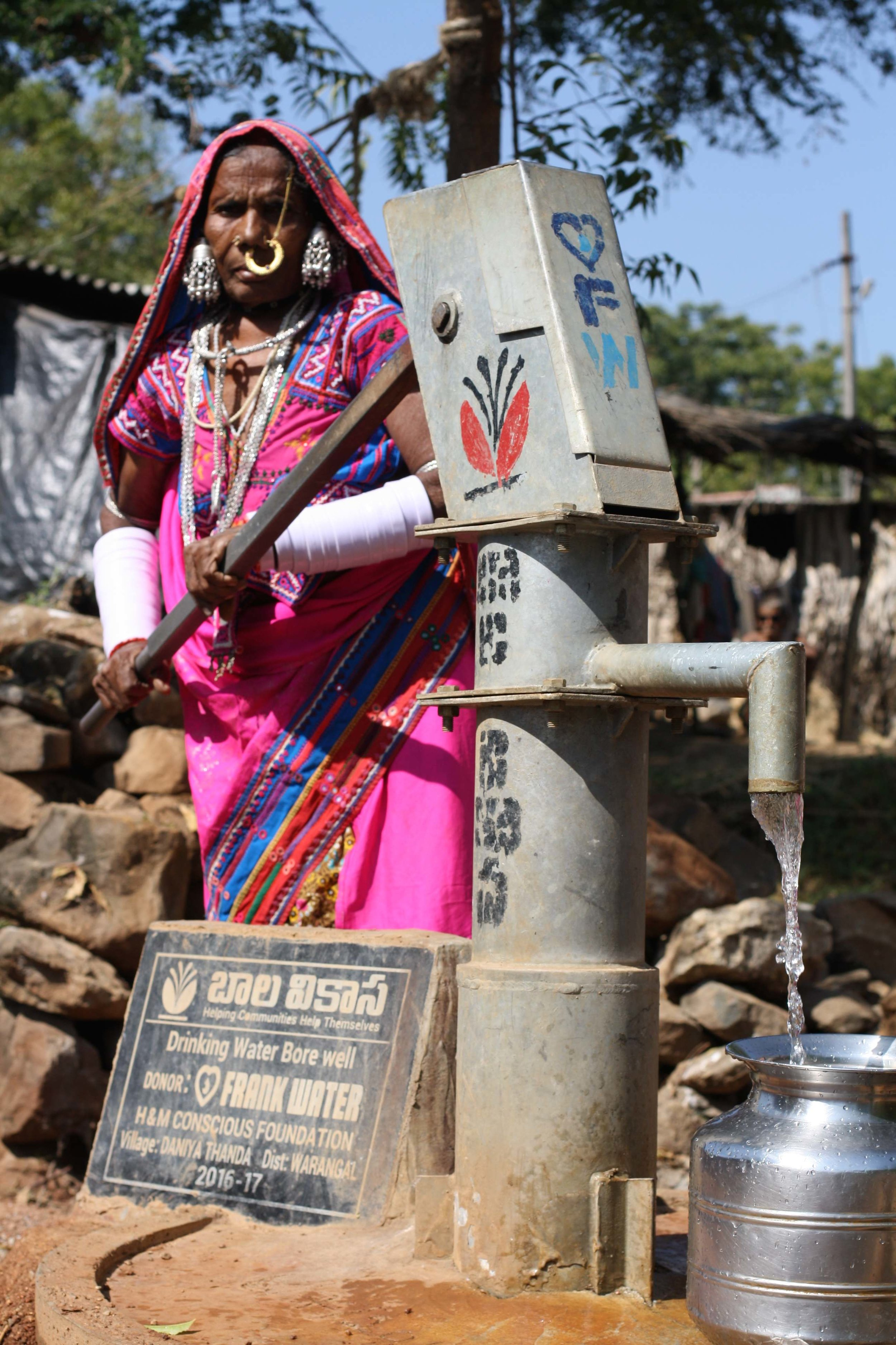 Tribal woman collects water from FRANK Water handpump