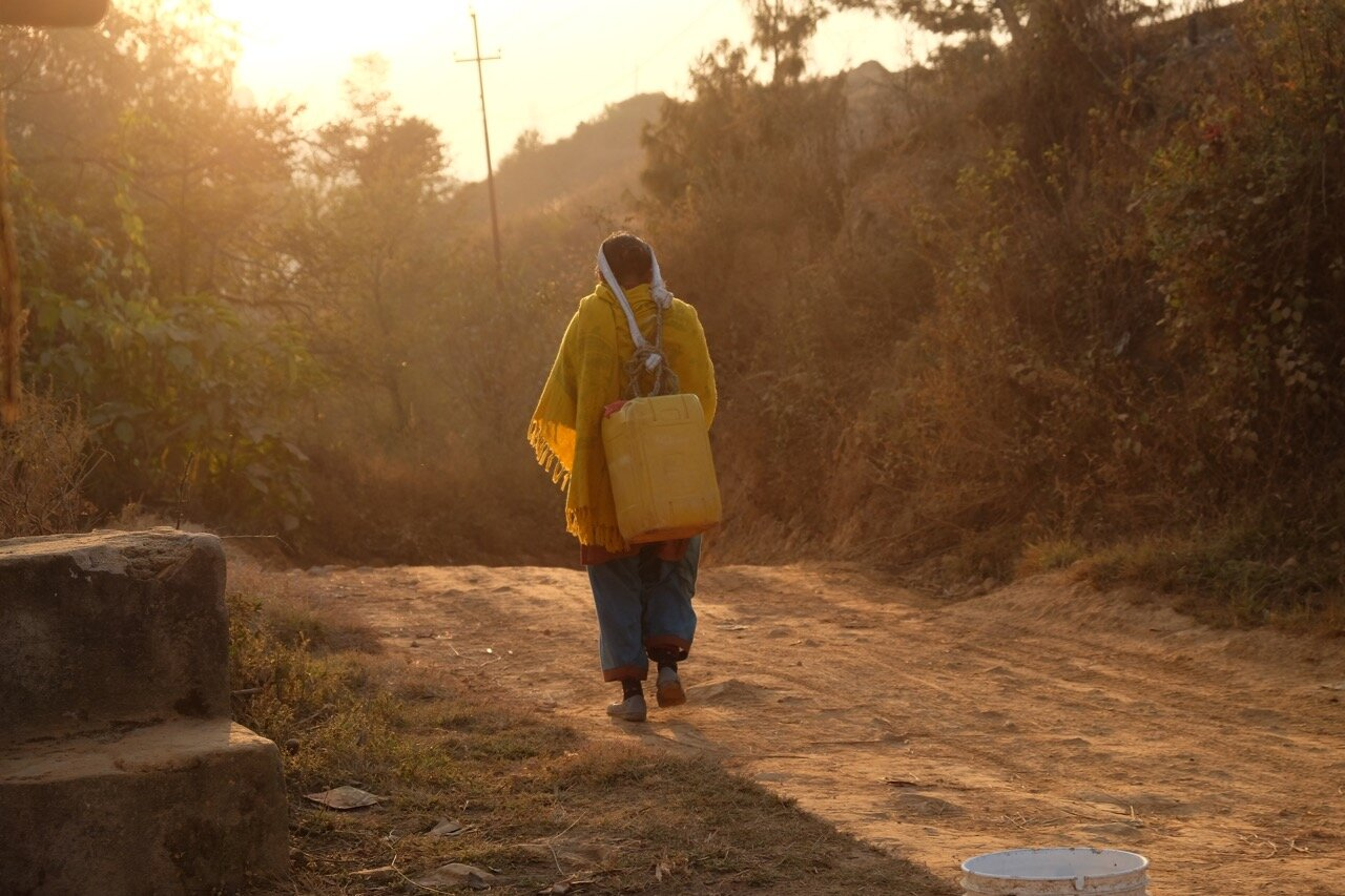 Carrying water containers, sun setting.jpg