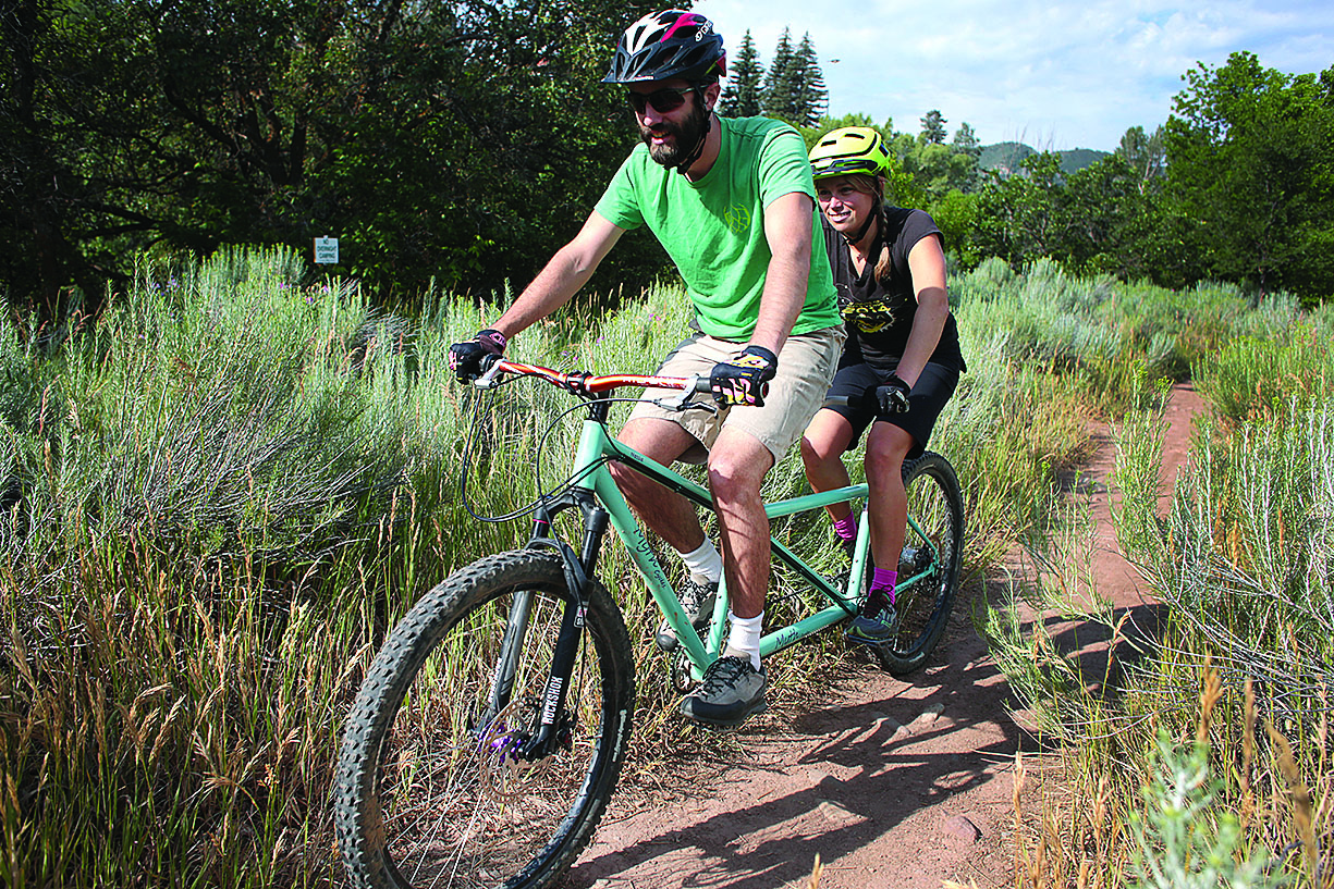 Newly betrothed husband and wife Eric and Hayley Tomczak take Nessie, Eric's hand-crafted creation, out for a spin. A welder by trade, Eric recently started Myth Cycles, a hand-built bicycle company, in Durango. He makes single-seated bikes, too./Photo by Jennaye Derge
