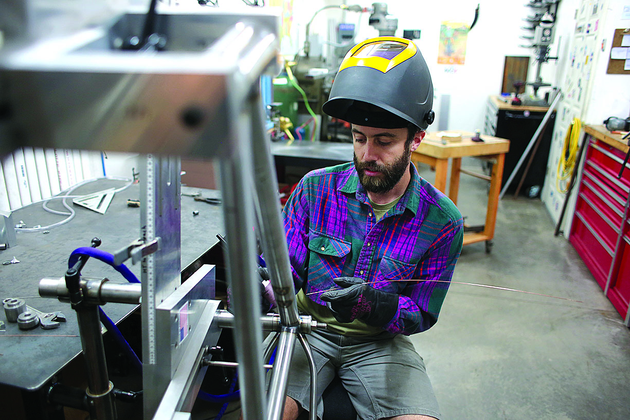 Eric Tomczak welds a frame in his shop. He works in steel for its longevity, versatility and absorption./Photo by Jennaye Derge