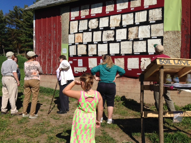 Participants during the Farm Art Dtour visiting the soil quilt exhibit. Photo by Leslee Nelson