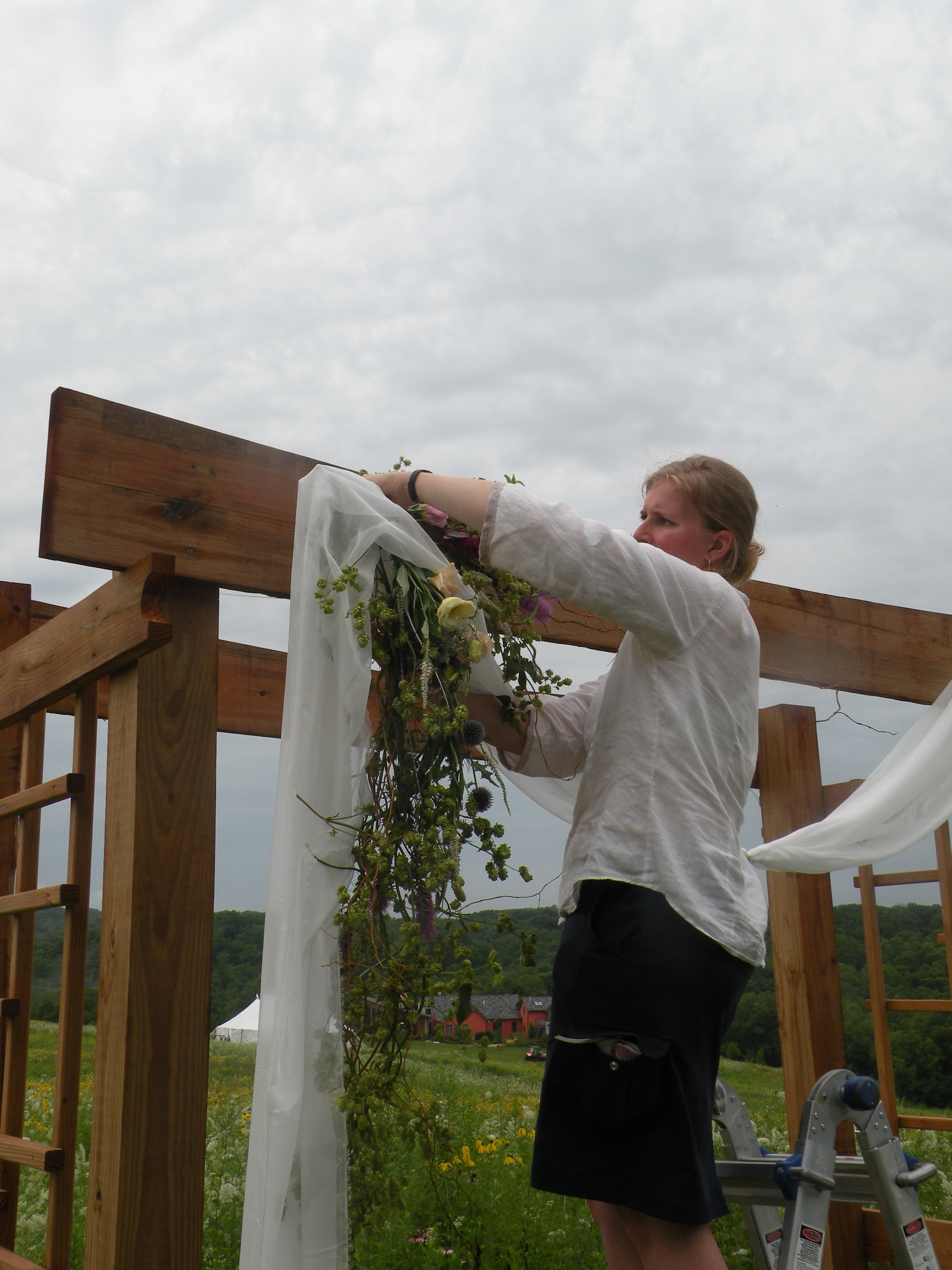 Mary Jo, helping install arbor floral decor, just before the next round of thunderstorms. Photo by Erin Schneider