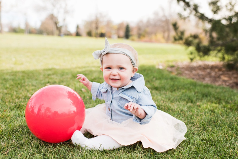 A baby girl with a bright colored ball sits in the warm fall light.  Film portraits by Sonja Salzburg of Sonja K Photography.