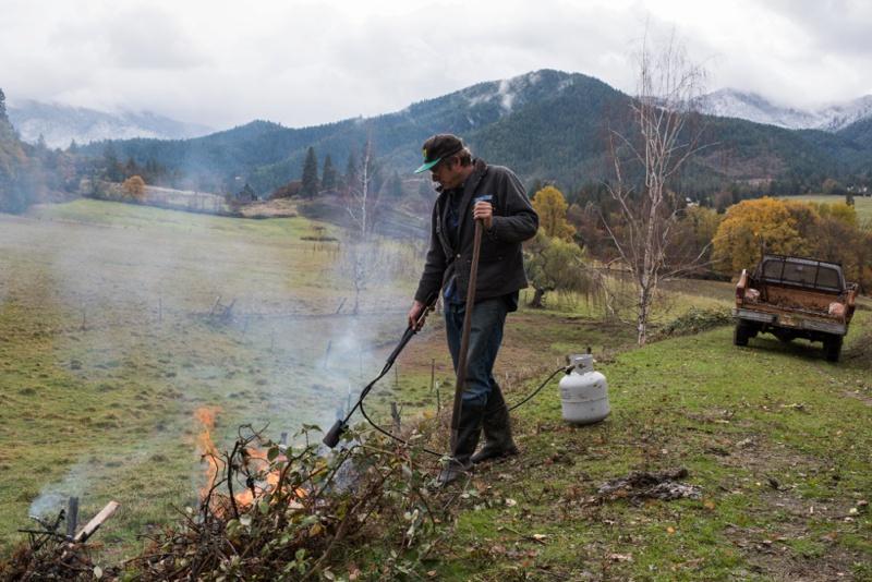 A rancher burns blackberry bushes on his lush Oregon ranch. Film portraits by Sonja Salzburg of Sonja K Photography.