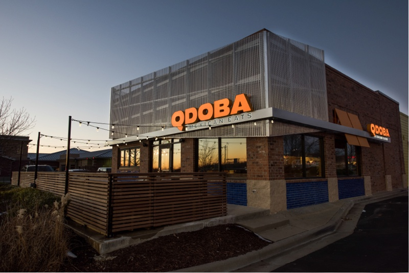 A redesigned and updated Qdoba Mexican Eats location in Omaha, Nebraska reflects the warm orange glow of sunset in its windows. Corporate photography by Sonja Salzburg of Sonja K Photography.