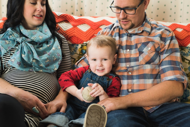 an adorable boy smiles at the camera while being held by his hip parents. Film photography by Sonja Salzburg of Sonja K Photography.