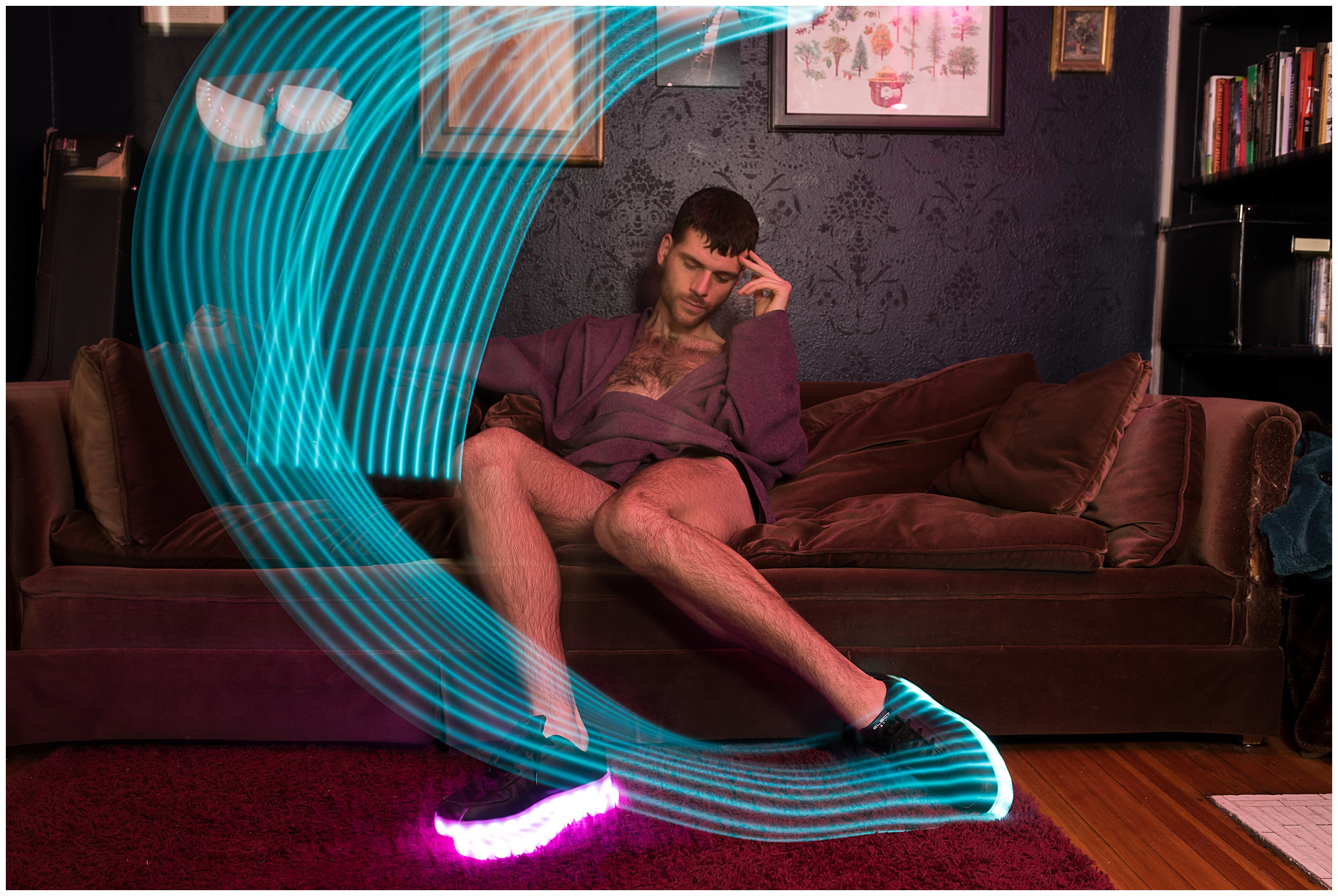 Sonja Salzburg of Sonja K Photography portrait of a dancer with light up shoes in motion on a brown couch in an LGBTQ house in Denver, Colorado.