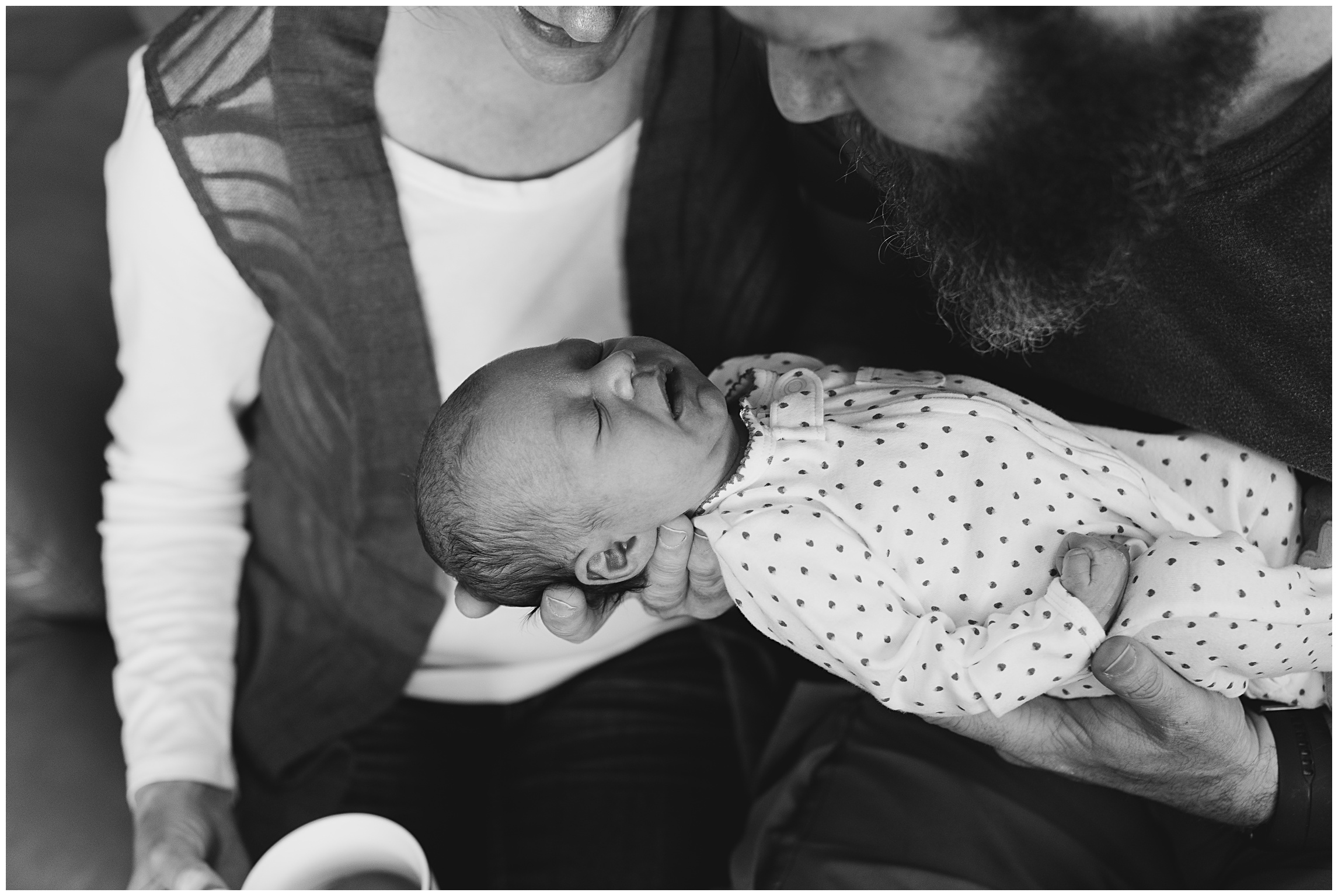 A mother and father hold their sleeping newborn baby girl. Film family photography by Sonja Salzburg of Sonja K Photography.
