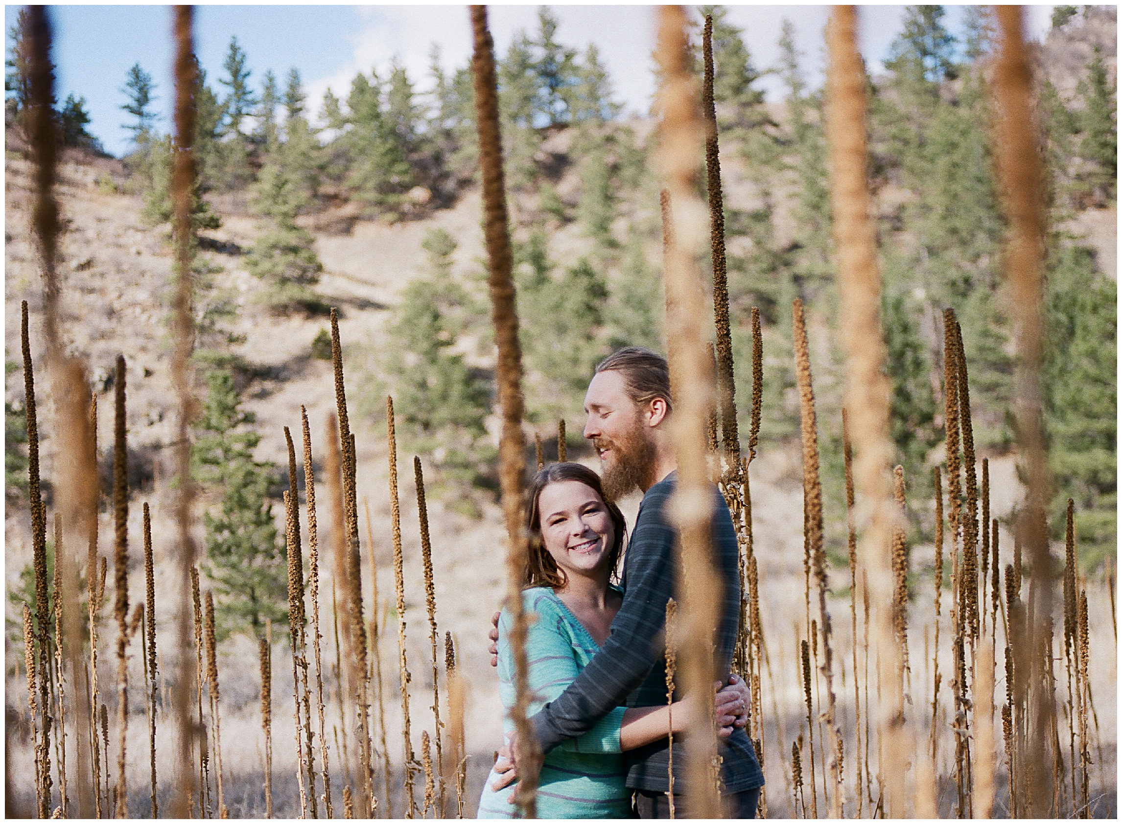 A young couple lovingly holding each other in the bright fall light. Engagement photography by Sonja Salzburg of Sonja K Photography.