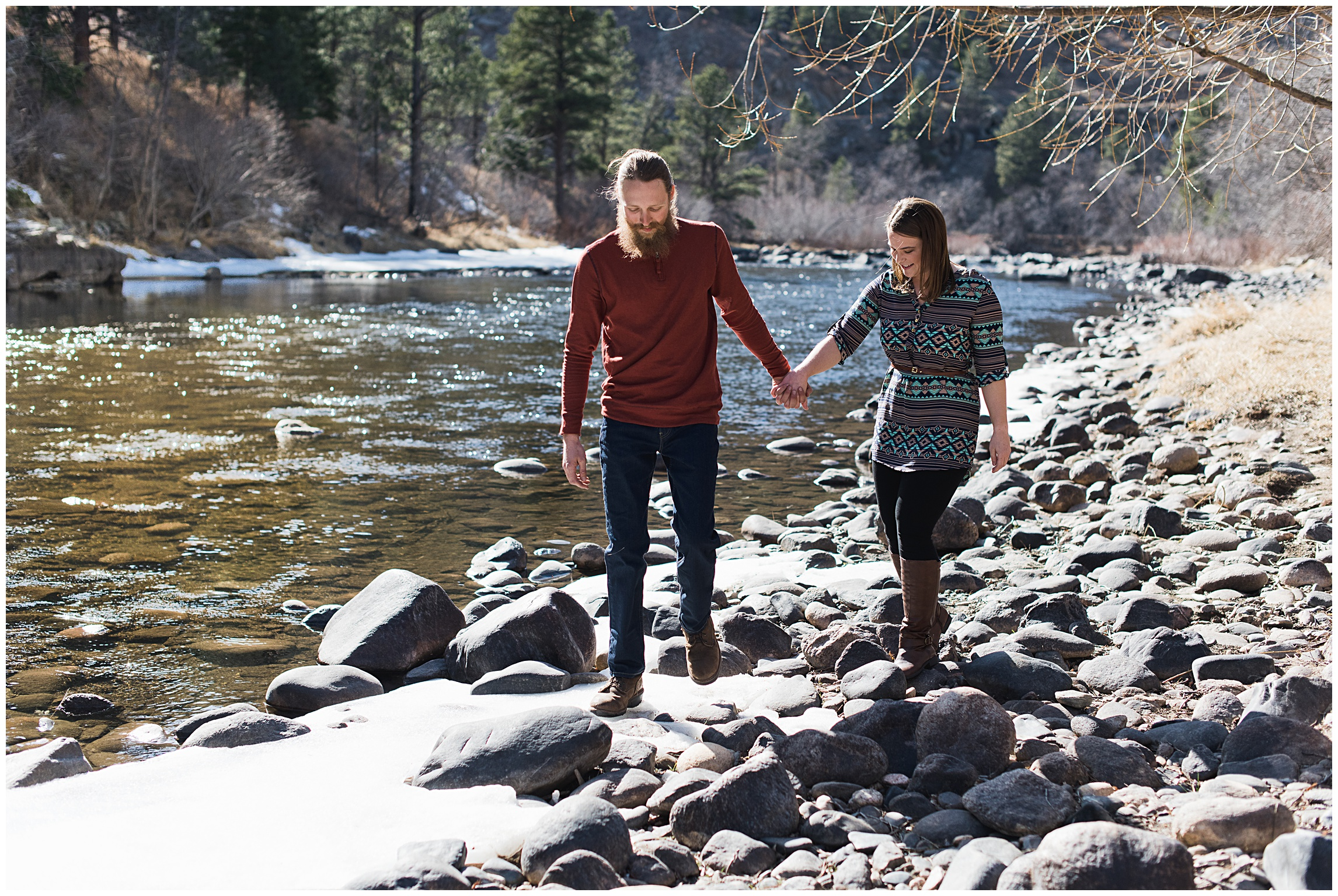 A young couple walk on the grey rocks next to a river on a sunny fall day. Engagement photography by Sonja Salzburg of Sonja K Photography.