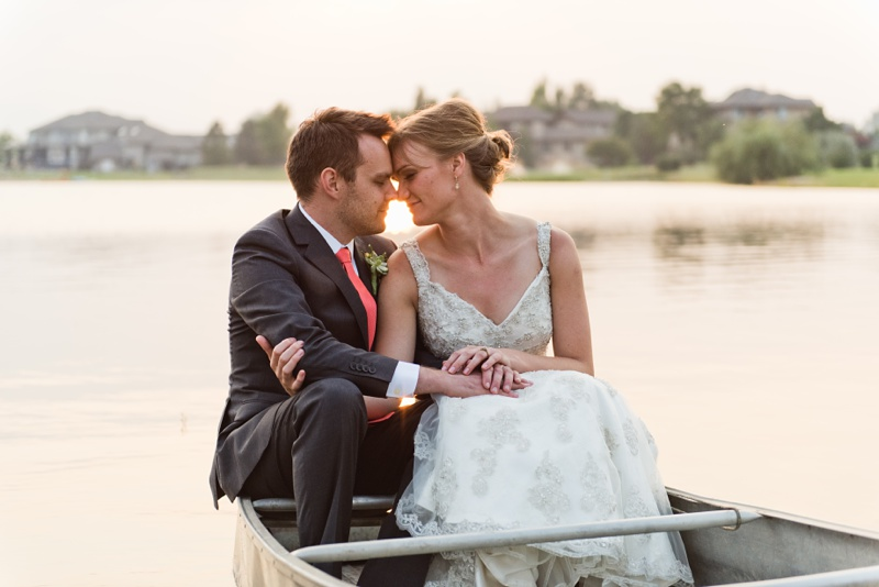 A warm spring evening with as bride and groom in a canoe on a Colorado lake at sunset. Wedding photography by Sonja Salzburg of Sonja K Photography.