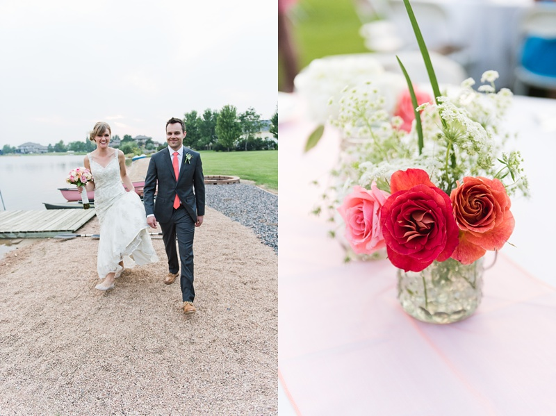 A happy bride and groom walk on a beach by a lake in Colorado. A bright warm red, pink, and orange rose centerpiece. Wedding photography by Sonja Salzburg of Sonja K Photography.