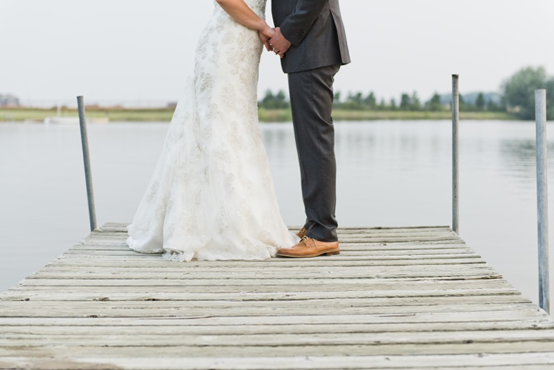 A newly married couple share a moment at the end of a dock in Colorado. Wedding photography by Sonja Salzburg of Sonja K Photography.