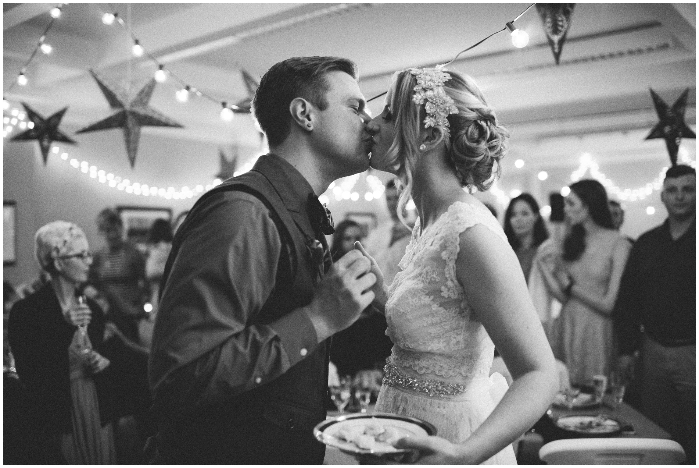 A bride and groom kiss in a black and white photograph. Wedding photography by Sonja Salzburg of Sonja K Photography.