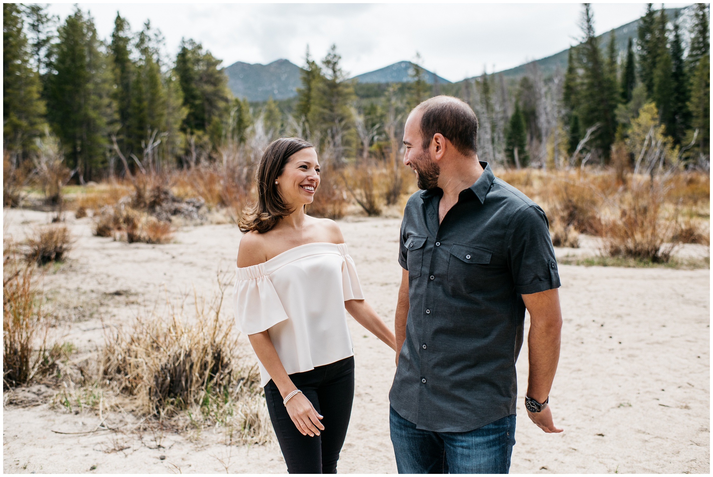 A loving couple on the beach at Sprague Lake in Rocky Mountain National Park. Engagement photography by Sonja Salzburg of Sonja K Photography.