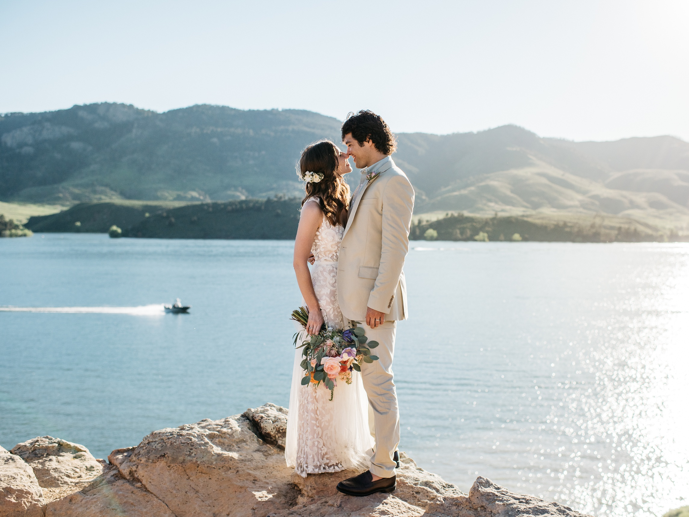 A newly married bride and groom at Horsetooth Reservoir in Fort Collins, Colorado. Wedding photography by Sonja Salzburg of Sonja K Photography.