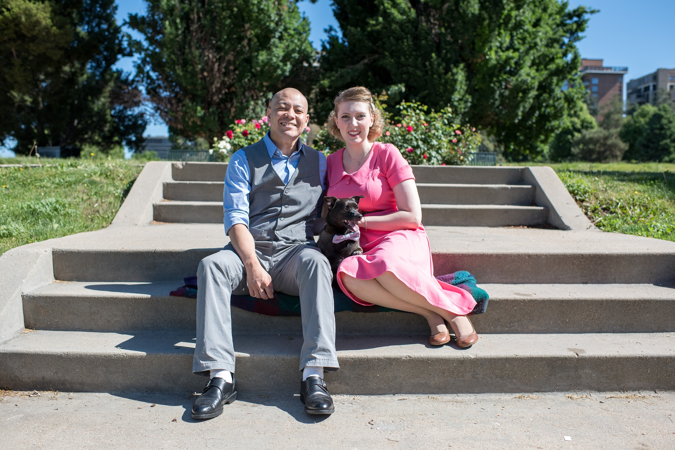 A cute engaged couple with their dog at Cheesman Park in Denver, Colorado. Engagement photography by Sonja Salzburg of Sonja K Photography.