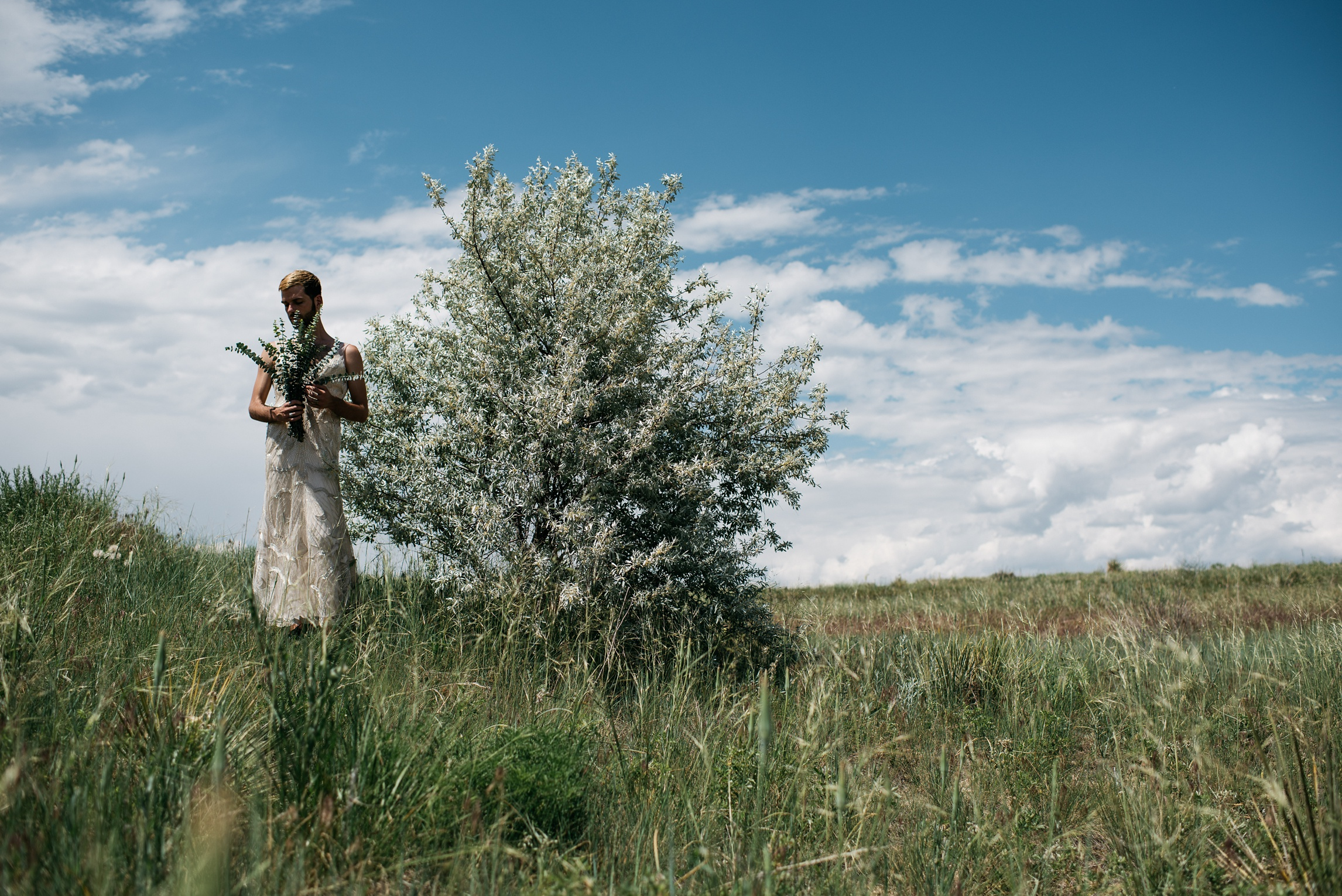 Ryan Page, a scorned bride in a Maggie Sottero wedding dress near an olive tree, holding a eucalyptus bouquet. Photography by Sonja Salzburg of Sonja K Photography.
