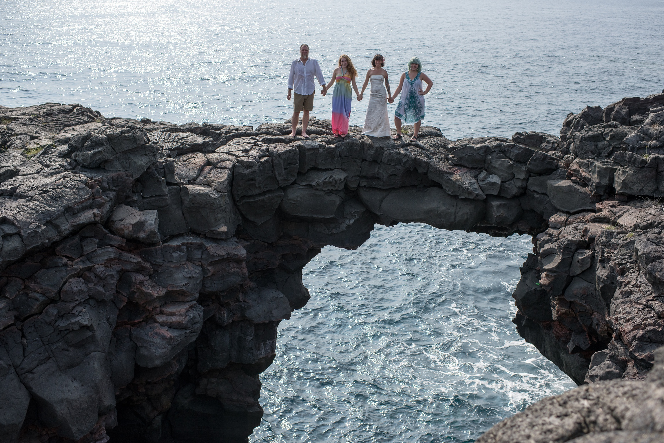 The family on top of a sea arch near Naalehu, Hawaii. Anniversary portrait photography by Sonja Salzburg of Sonja K Photography.