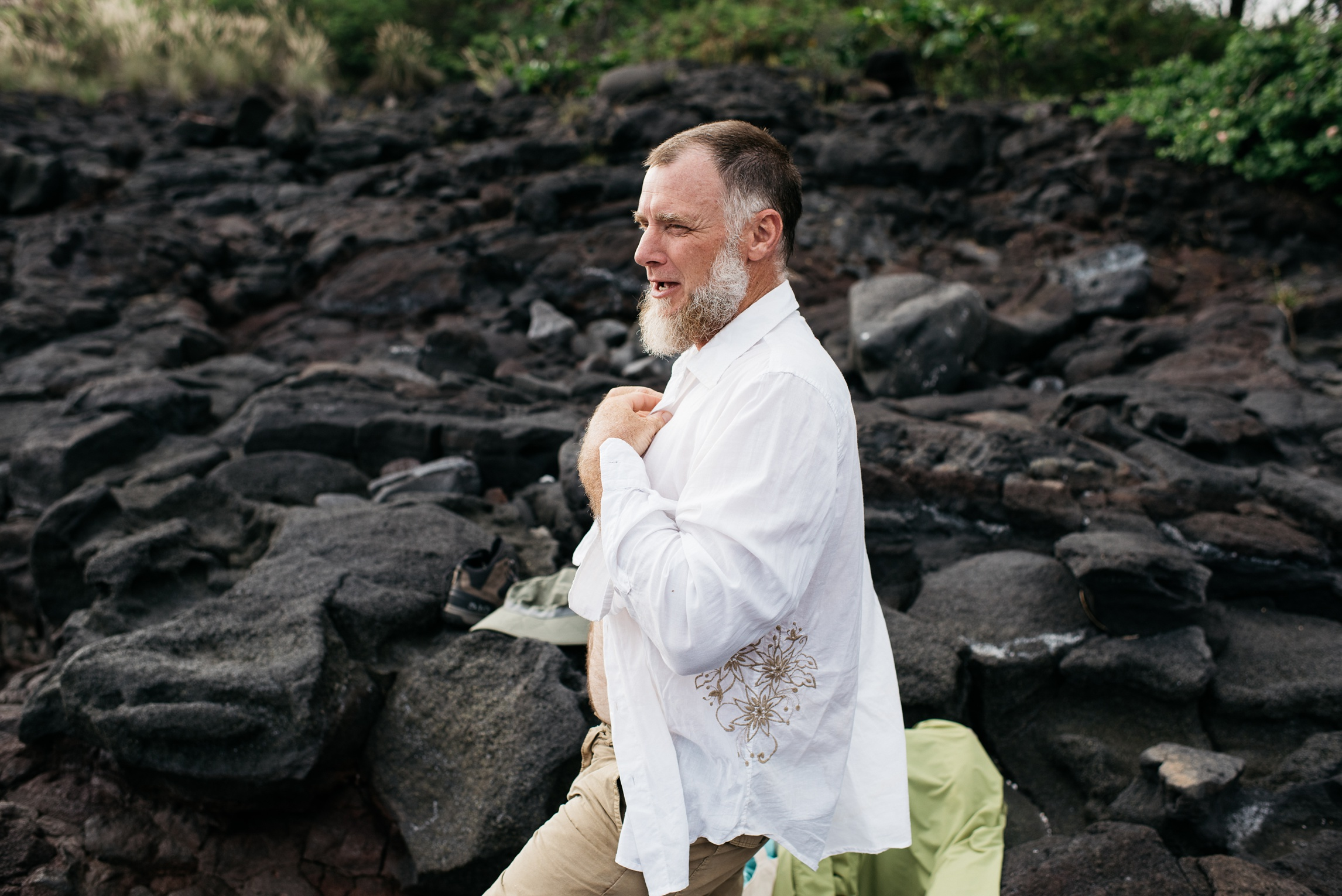 Dan prepares to climb up the lava to a high point above the beach near Naalehu, Hawaii. Anniversary portrait photography by Sonja Salzburg of Sonja K Photography.