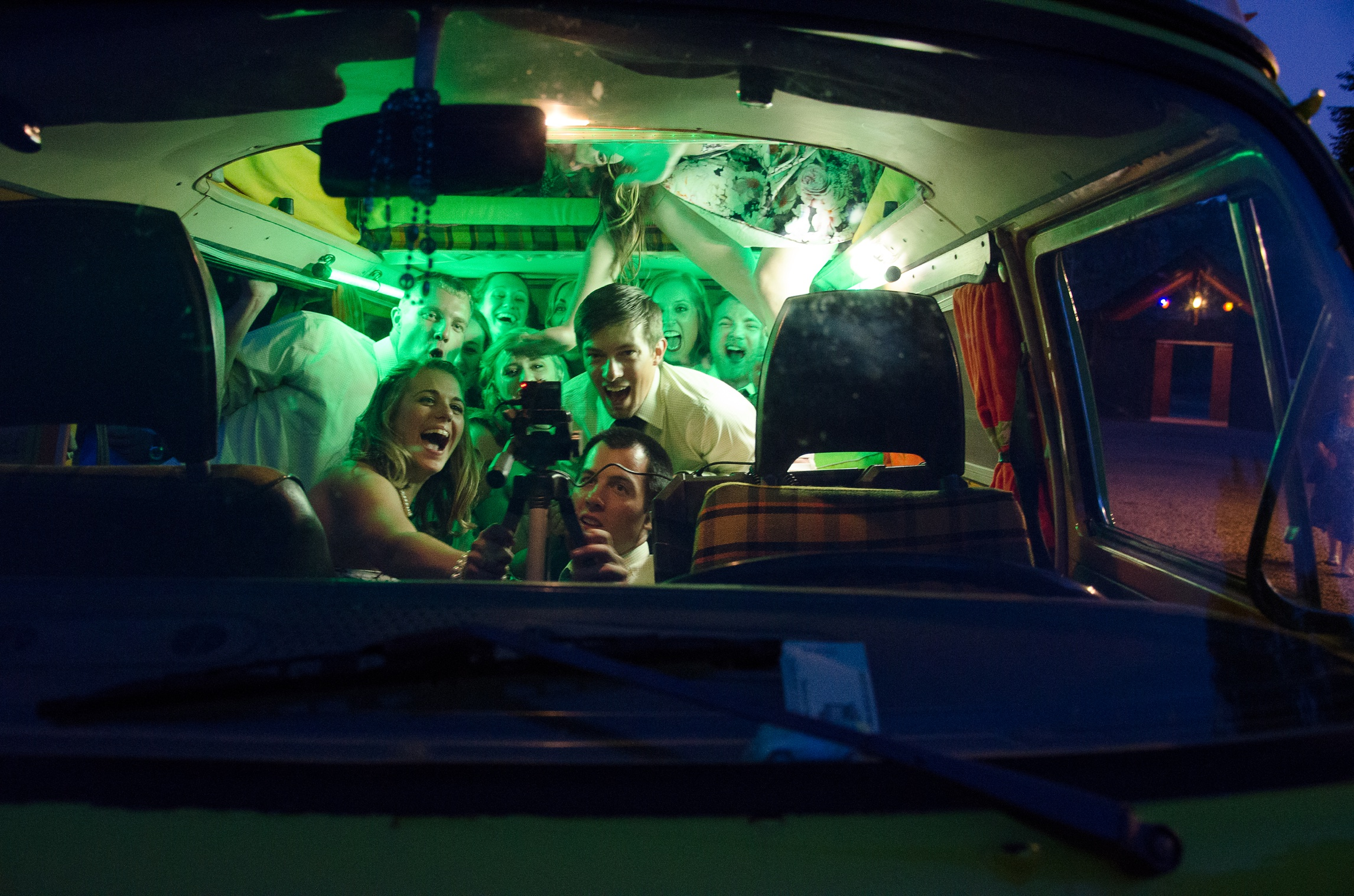 The wedding party piles into a vintage Volkswagen Bus to take photos at Planet Bluegrass in Lyons, Colorado. Wedding photography by Max Salzburg of Sonja K Photography.