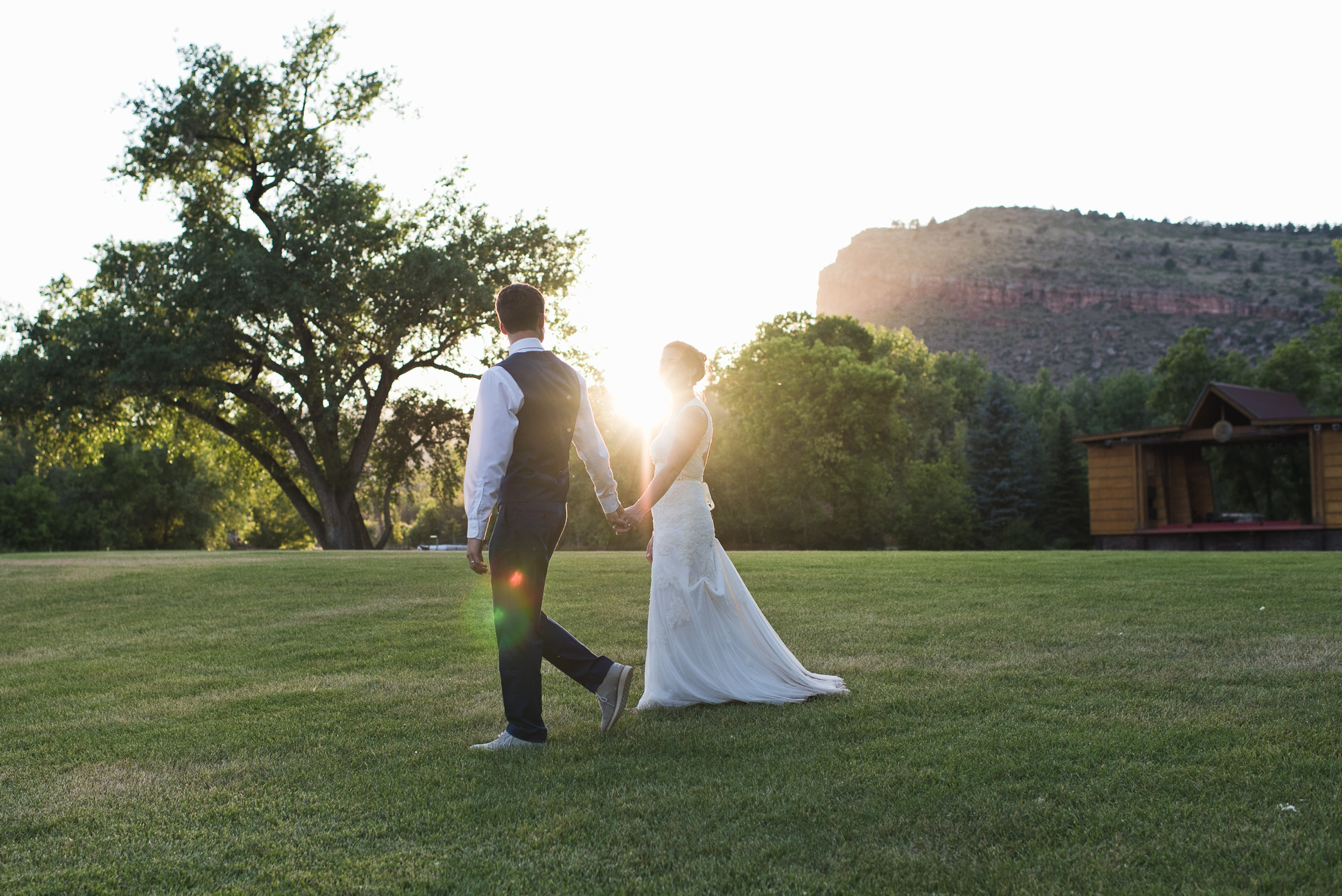 A bride and groom walk the grounds at Planet Bluegrass in Lyons, Colorado. Wedding photography by Sonja Salzburg of Sonja K Photography.