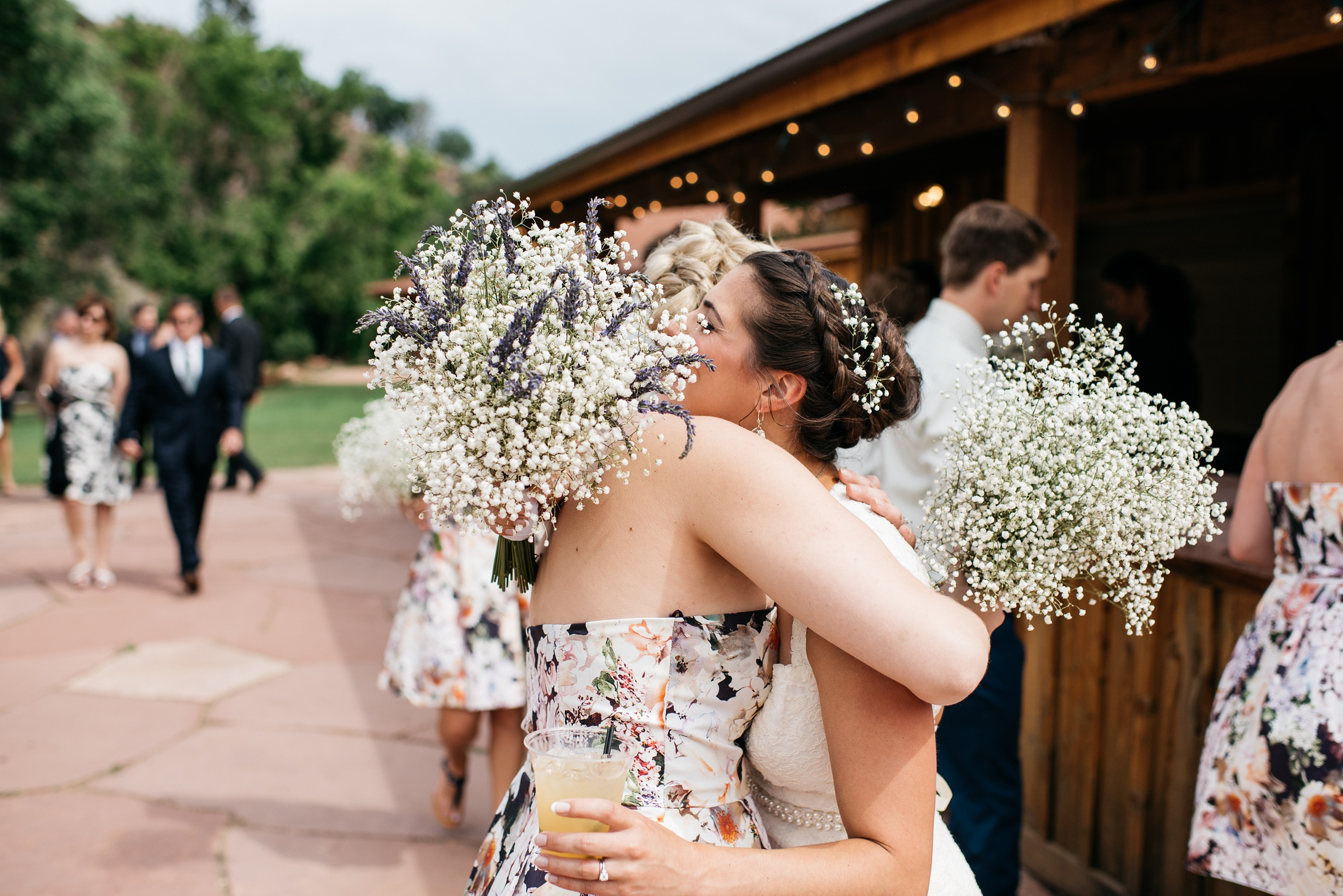 A bride and her bridesmaid embrace at a wedding at Planet Bluegrass in Lyons, Colorado. Wedding photography by Sonja Salzburg of Sonja K Photography.
