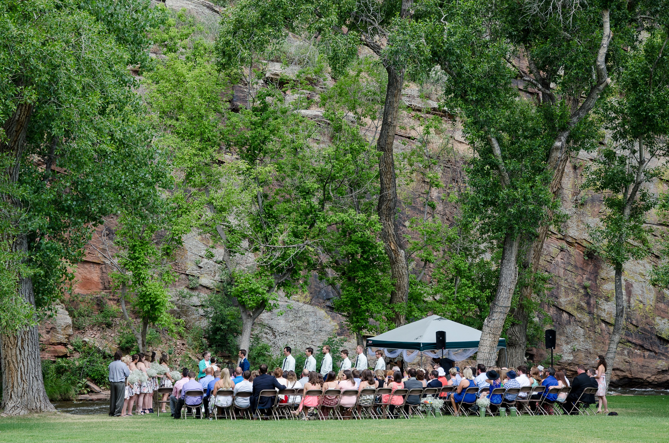 The wedding ceremony by the river at Planet Bluegrass in Lyons, Colorado. Wedding photography by Max Salzburg of Sonja K Photography.