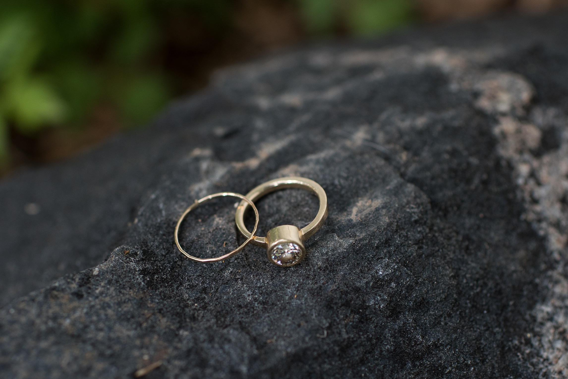 Bright gold wedding rings on a cool black rock. Wedding photography by Sonja Salzburg of Sonja K Photography.