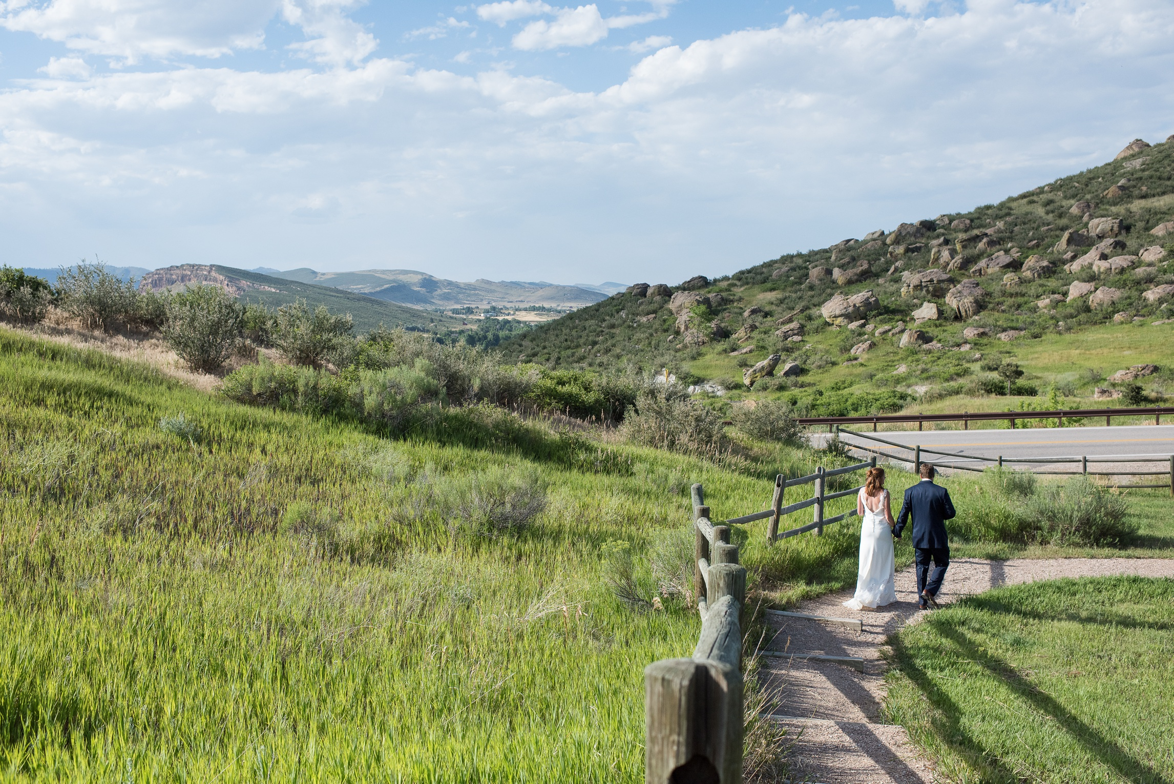 A bride and groom leave their wedding ceremony on top of Bingham Hill outside Fort Collins, Colorado. Wedding photography by Sonja Salzburg of Sonja K Photography.