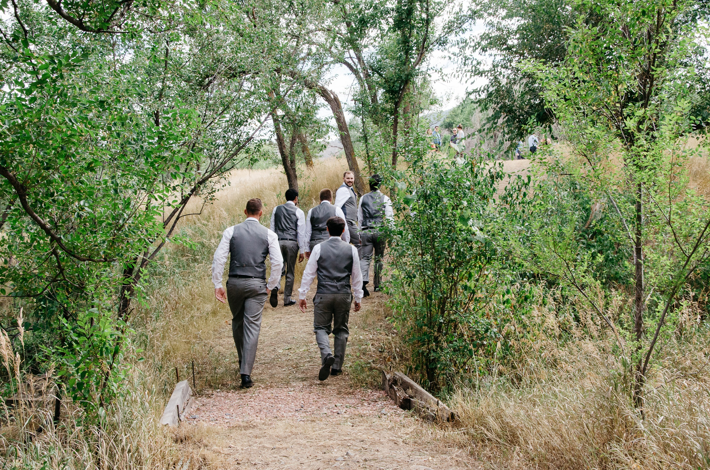 The groom and the groomsmen walk into the ceremony at Sylvan Dale Guest Ranch near Loveland, Colorado. Wedding photography by Sonja Salzburg of Sonja K Photography.