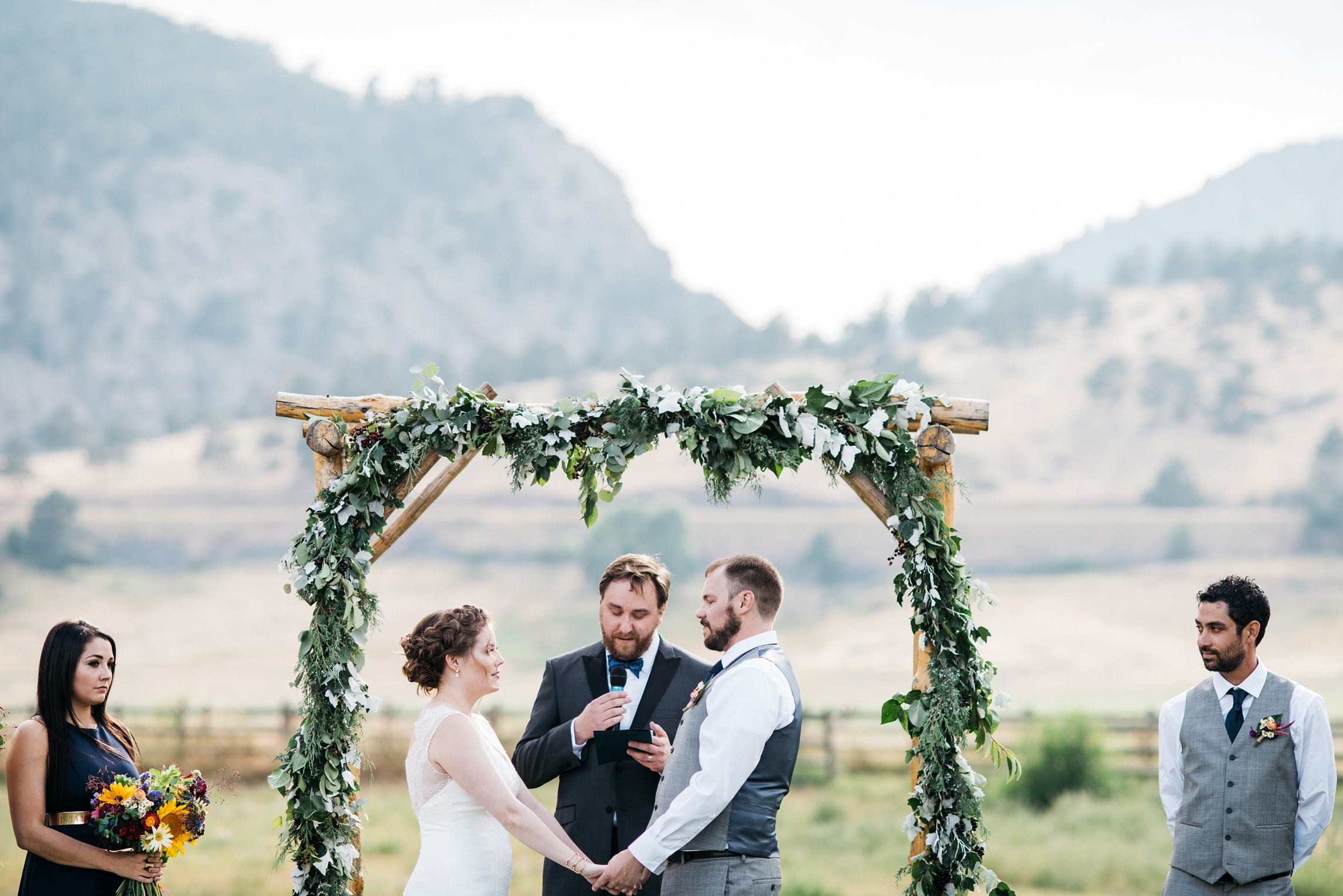 A bride and groom exchange vows on their wedding day at Sylvan Dale Ranch near Loveland, Colorado. Wedding Photography by Sonja Salzburg of Sonja K Photography.