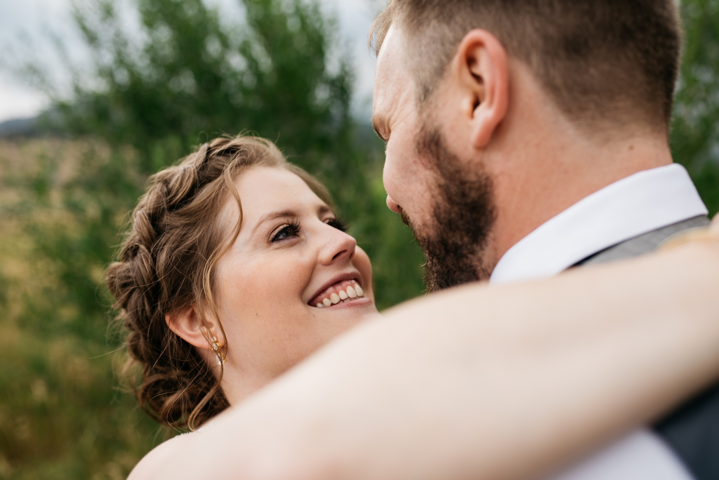 A bride and groom embrace on their wedding day at Sylvan Dale Guest Ranch outside Loveland, Colorado. Wedding photography by Sonja Salzburg of Sonja K Photography.
