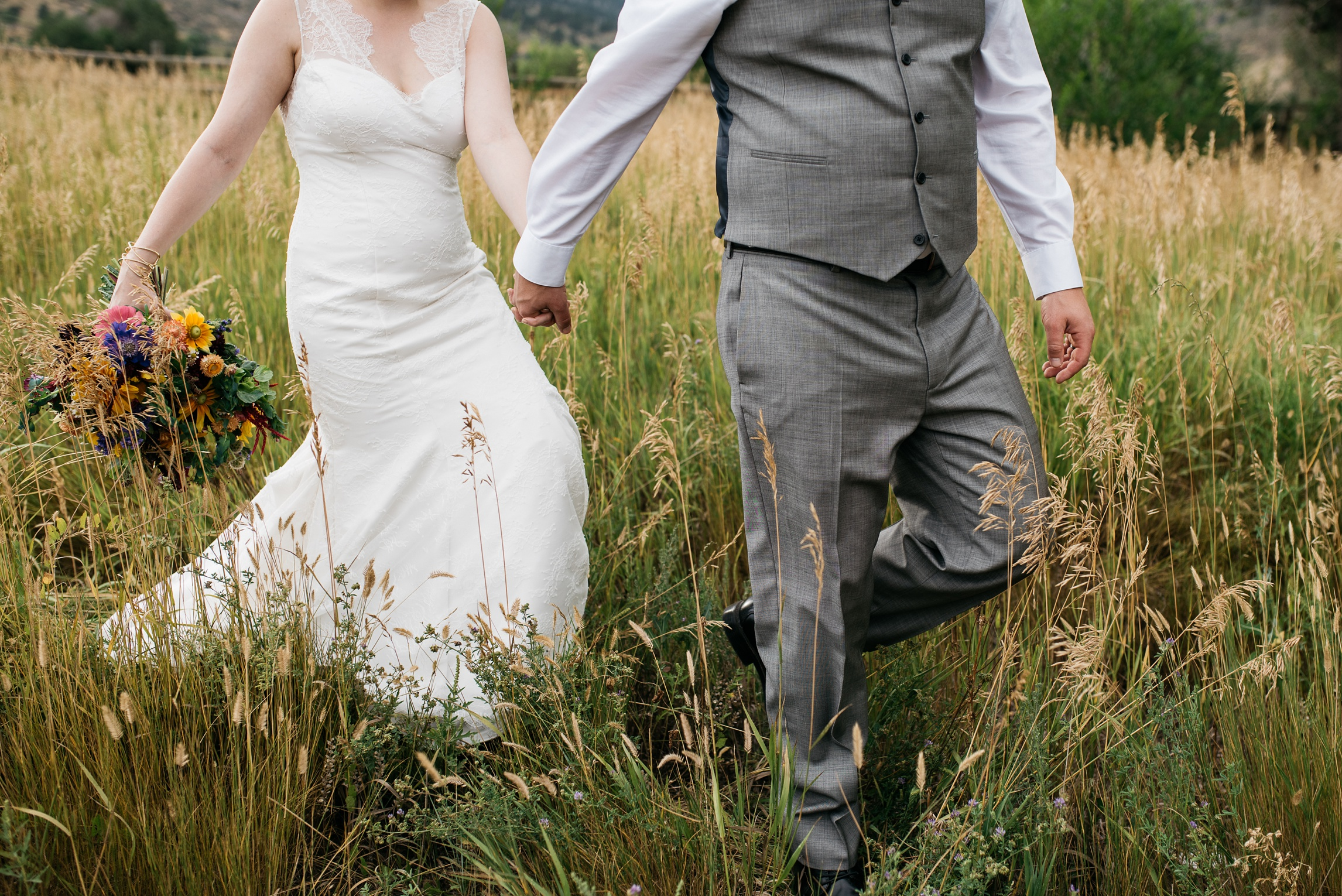 A bride and groom walk though the pastures at Sylvan Dale Guest Ranch on their wedding day. Wedding photography by Sonja Salzburg of Sonja K Photography.
