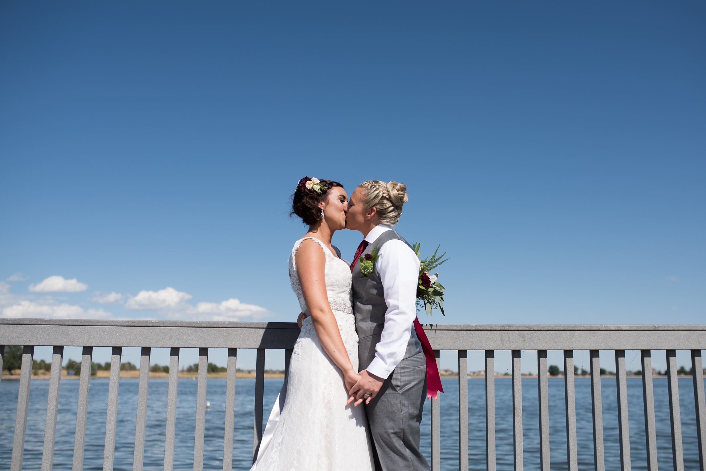 Two brides kiss after a reveal in Fort Collins, Colorado. Wedding photography by Sonja Salzburg of Sonja K Photography.