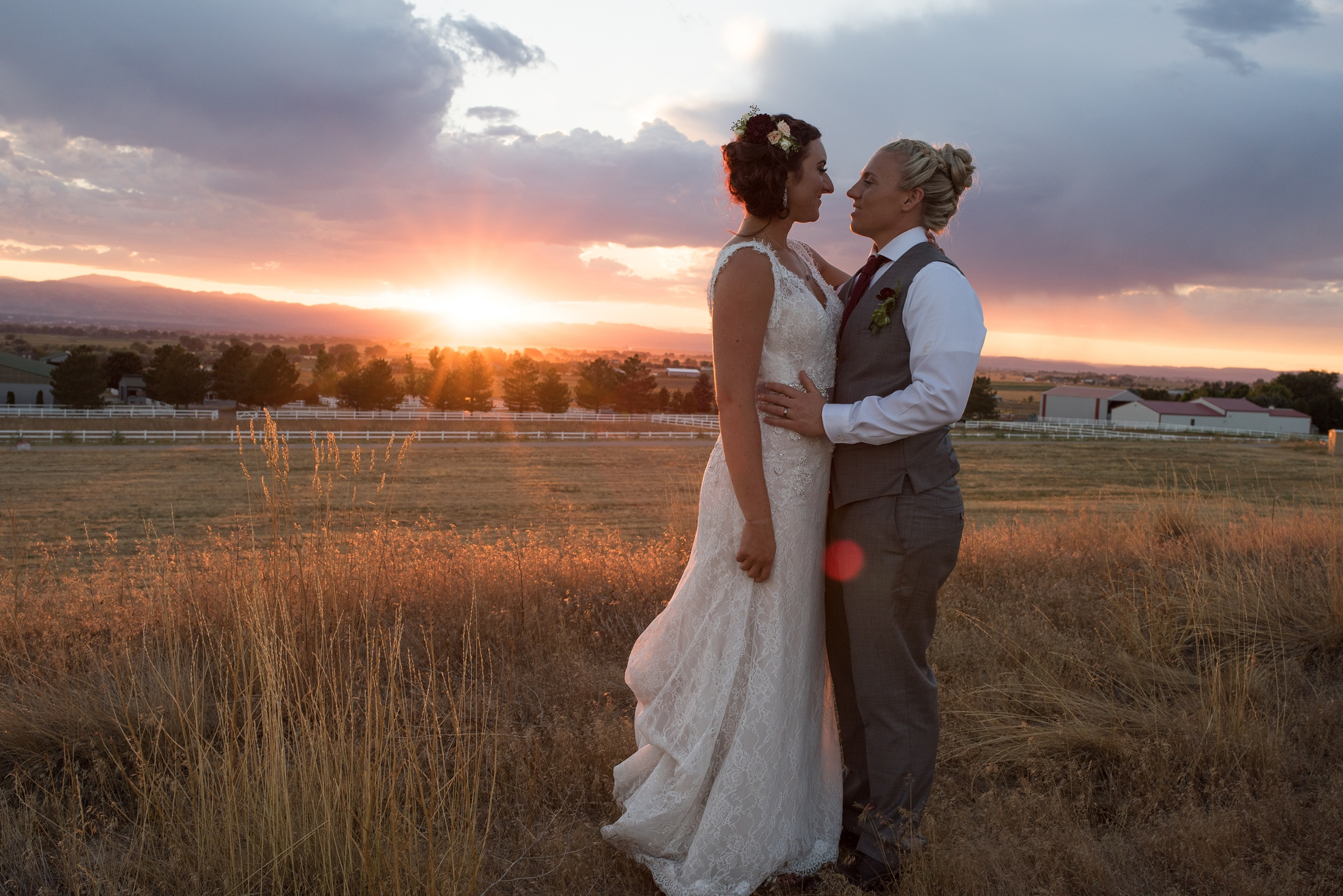 Two brides at sunset on their wedding day at Windsong Estate outside of Fort Collins, Colorado. Wedding photography by Sonja Salzburg of Sonja K Photography.