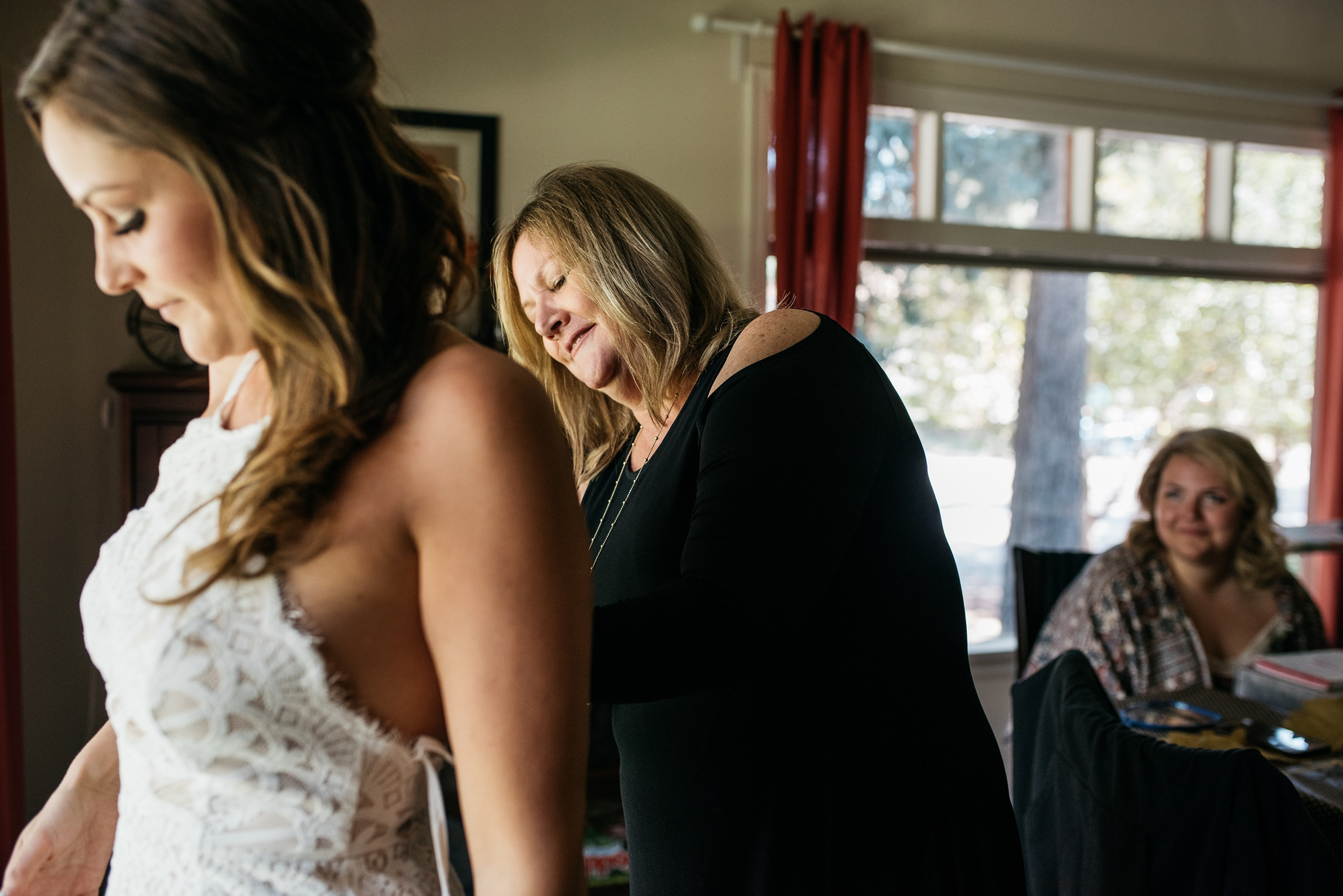 A bride puts on her wedding dress with help from her mother. Wedding photography by Sonja Salzburg of Sonja K Photography.